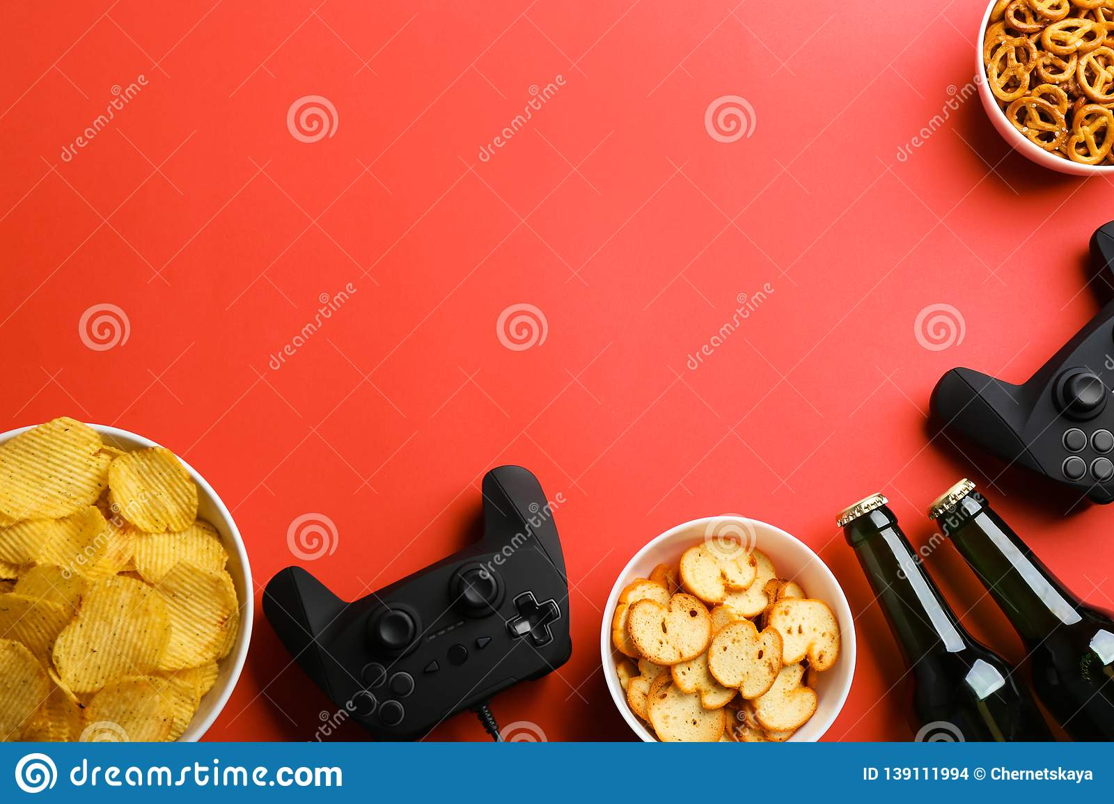 Flat lay composition with video game controllers, snacks and space for text
