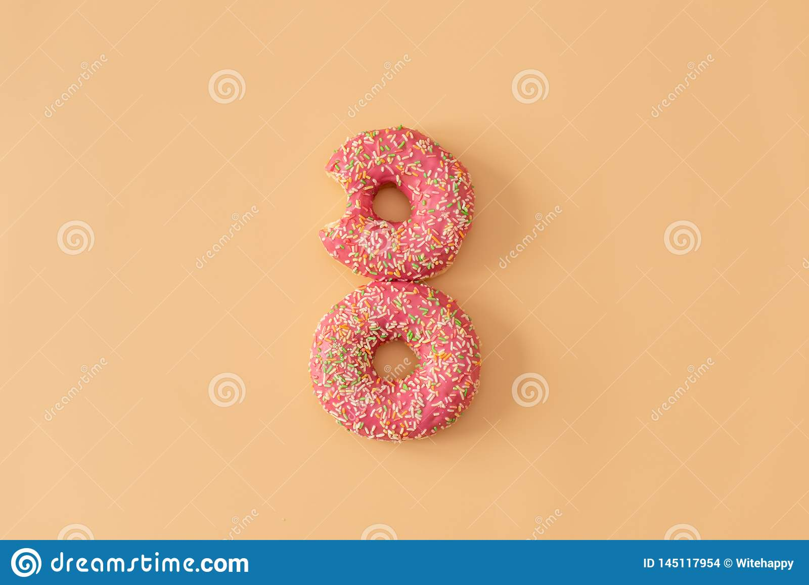 Flat lay donuts pattern on pastel orange background. Top view. Square crop. Sweet doughnut texture, copy space