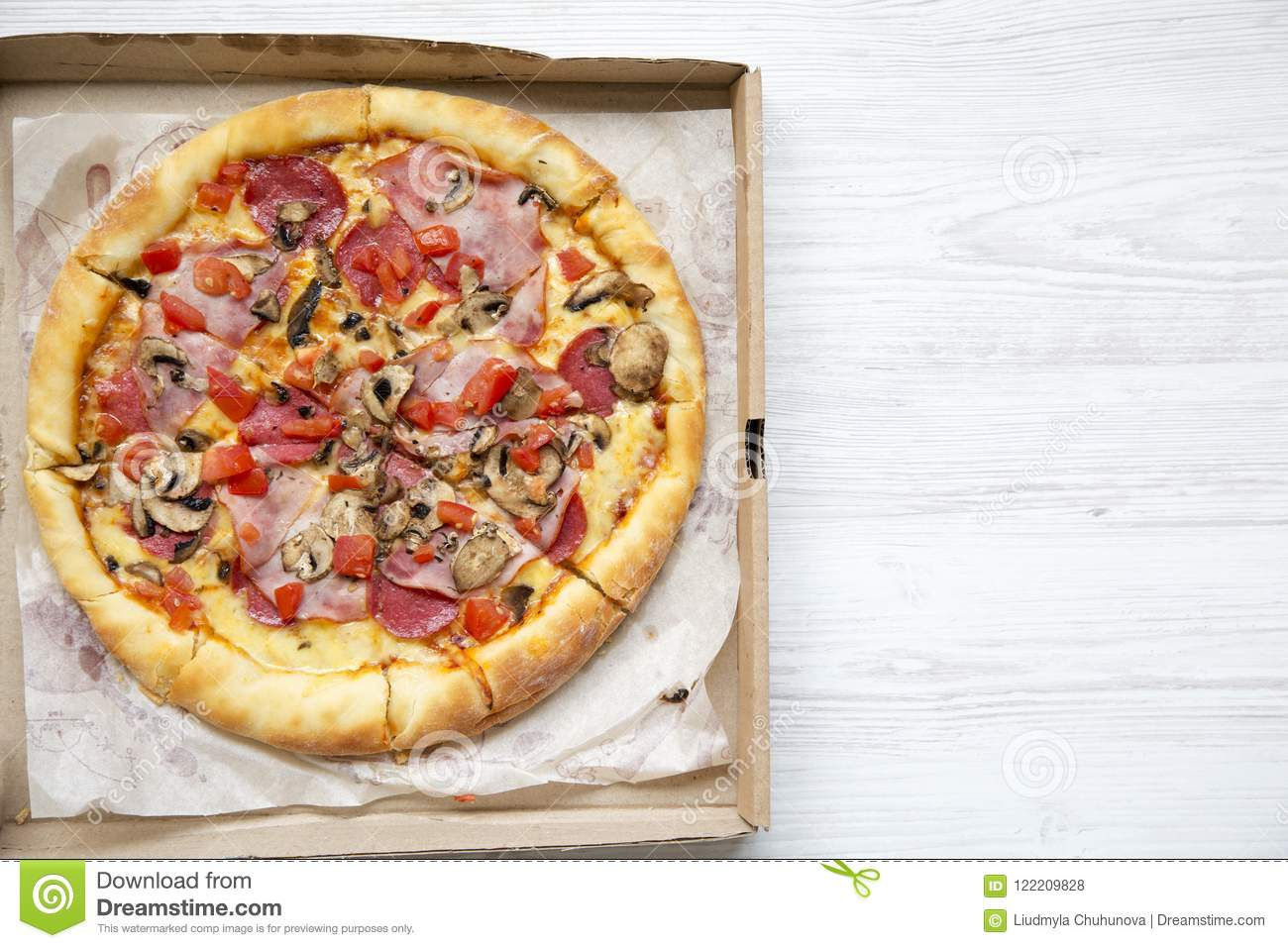 Flat Lay Of Fresh Pizza In A Cardboard Box On White Wooden