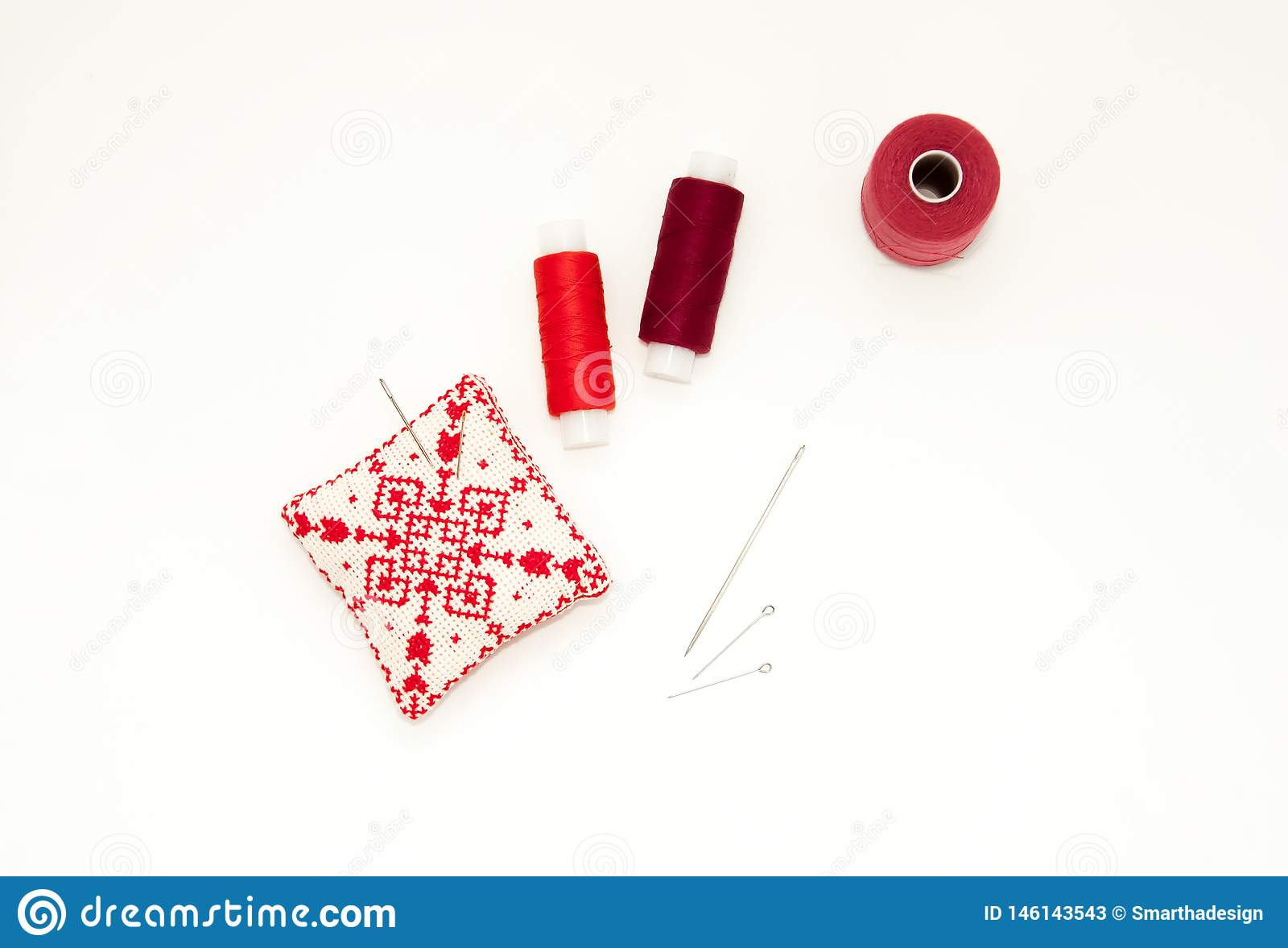 Flat lay with handmade red embroidered needle pad, thread spools, pins, needles, mock up, top view. Layout mockup on blank white