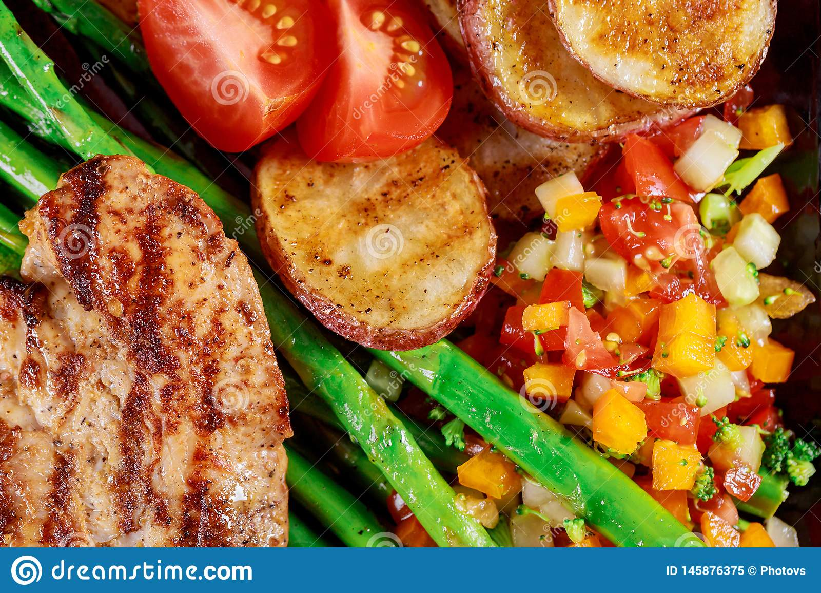 Flat-lay of healthy dinner fresh salad, grilled vegetables with grilled chicken breast
