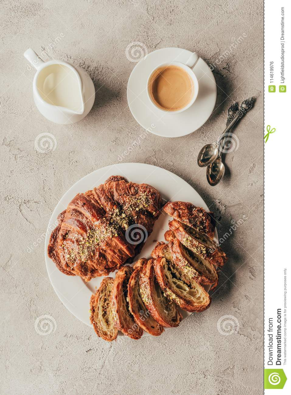 Flat lay with jug of milk, cup of coffee and sweet croissants with pistachio nuts on plate