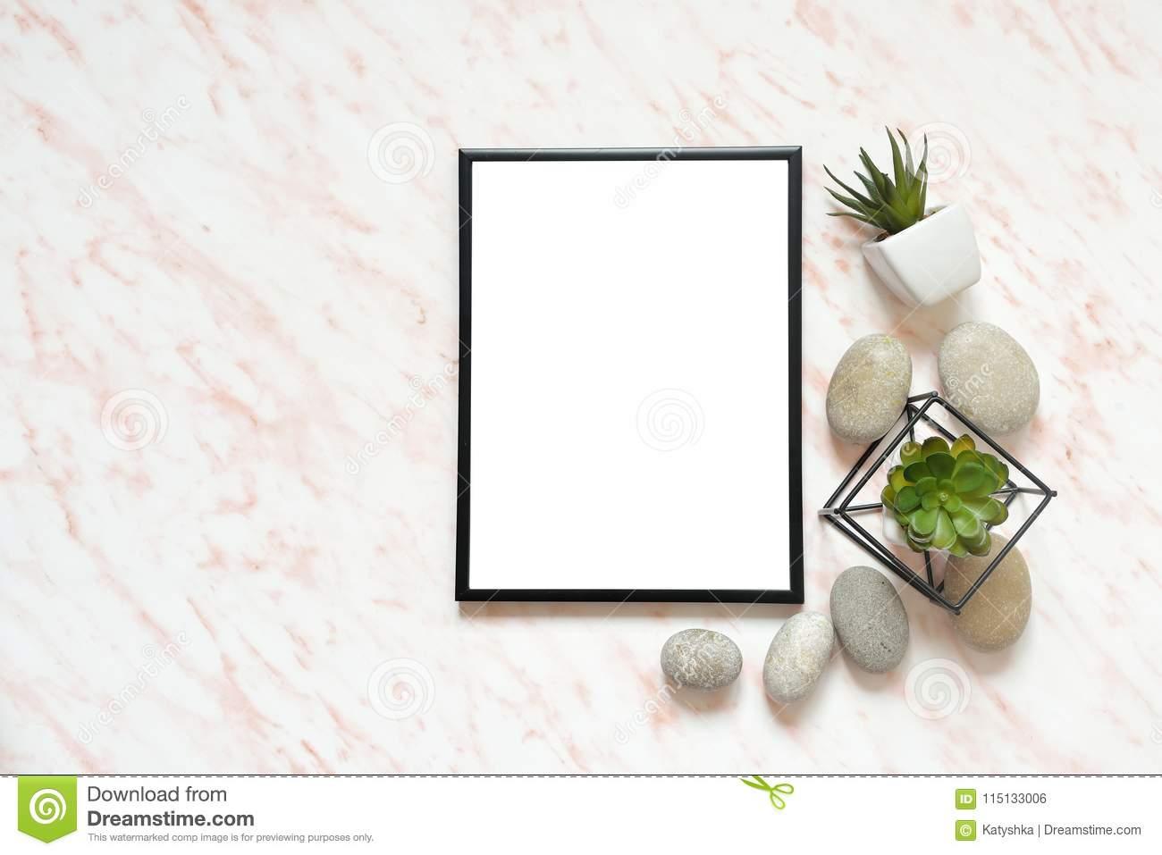 Flat lay marble desk with white empty frame for text, stones and succulents background