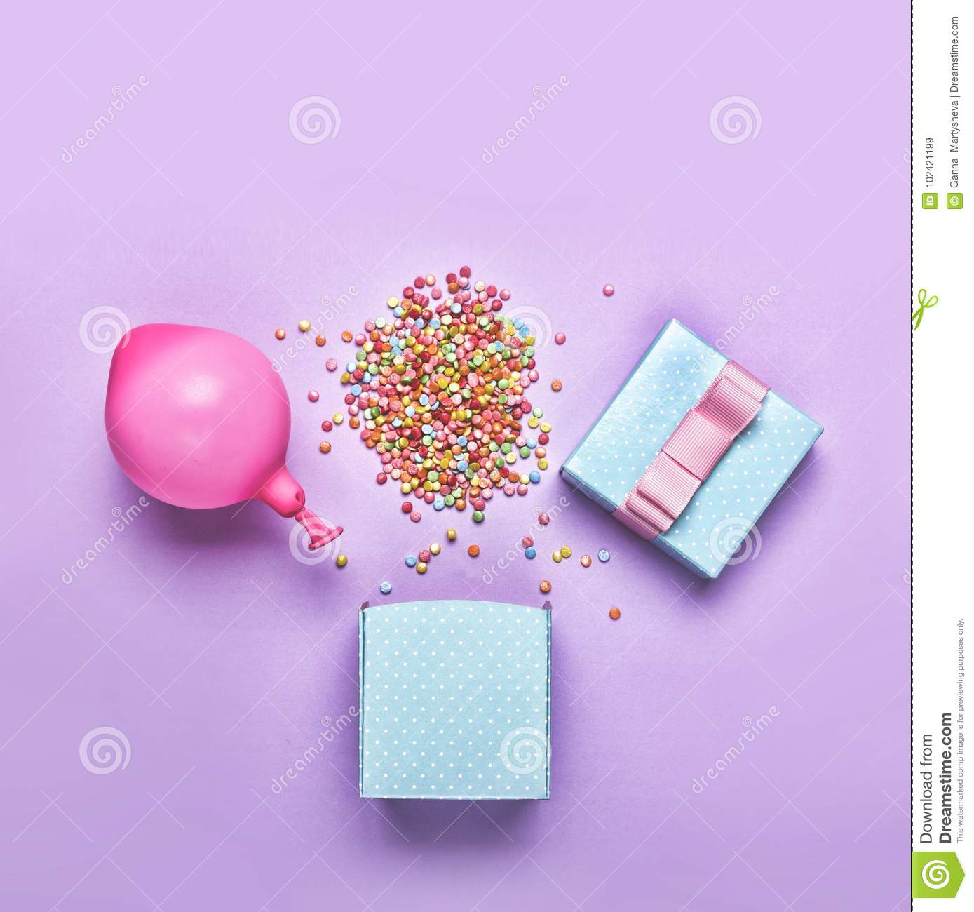 Flat lay.minimalism style, Blue gift box with various confetti parties, balloons, decorations on a green background. Colorful holi
