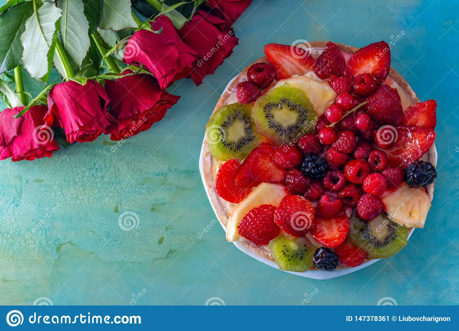 Flat-lay of red flowers roses and beautiful delicious sweet cake with berries on a green background. Greeting card