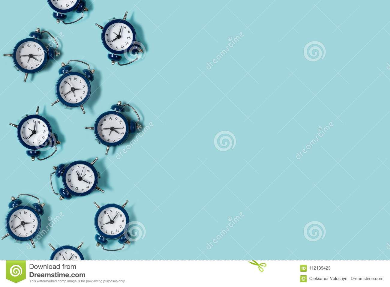 Flat lay retro beautiful new alarm clock on blue color background. Pattern.