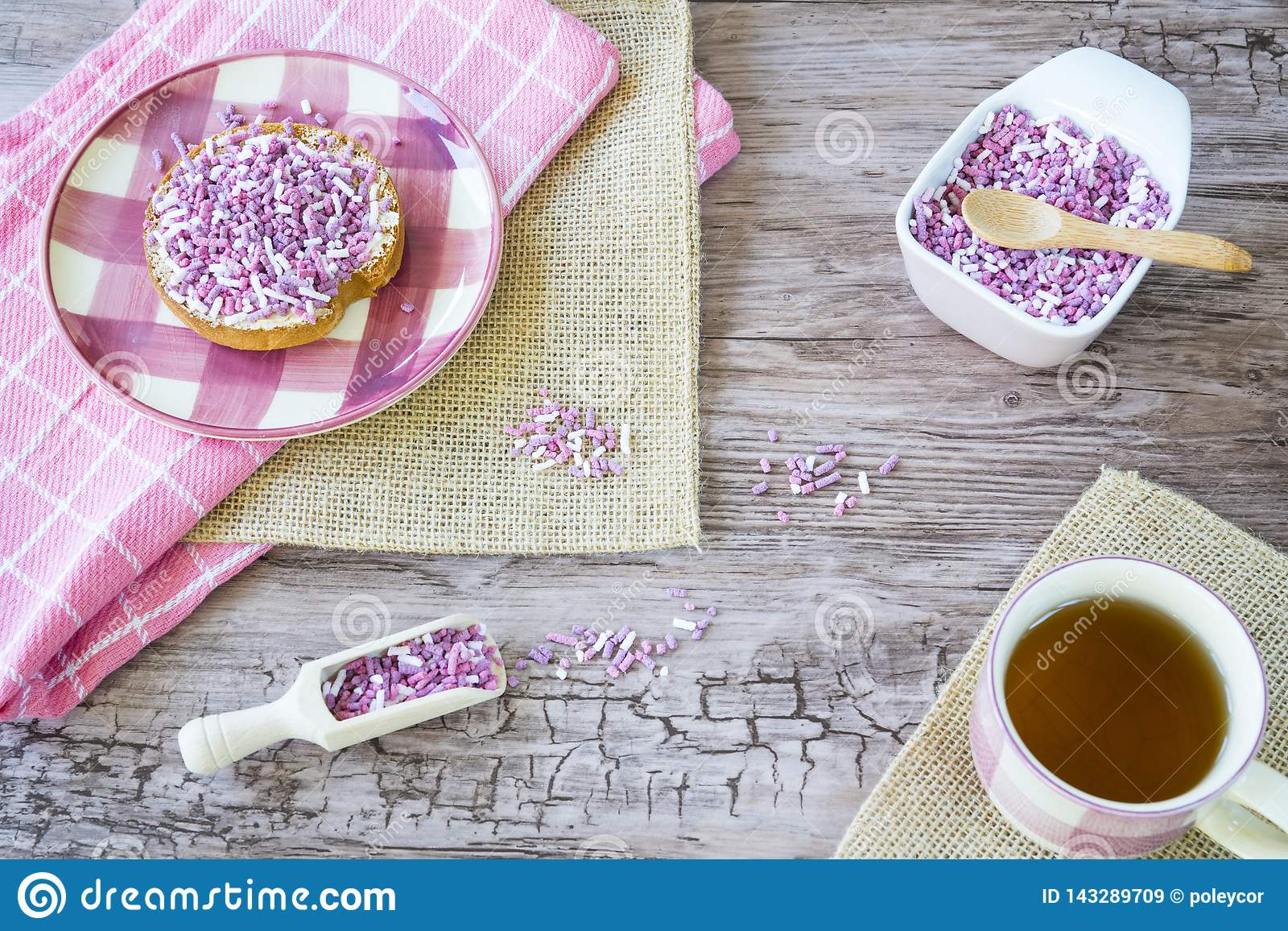 Flat lay with rusk, sweet pink purple sprinkles and cup of tea. Against wooden background