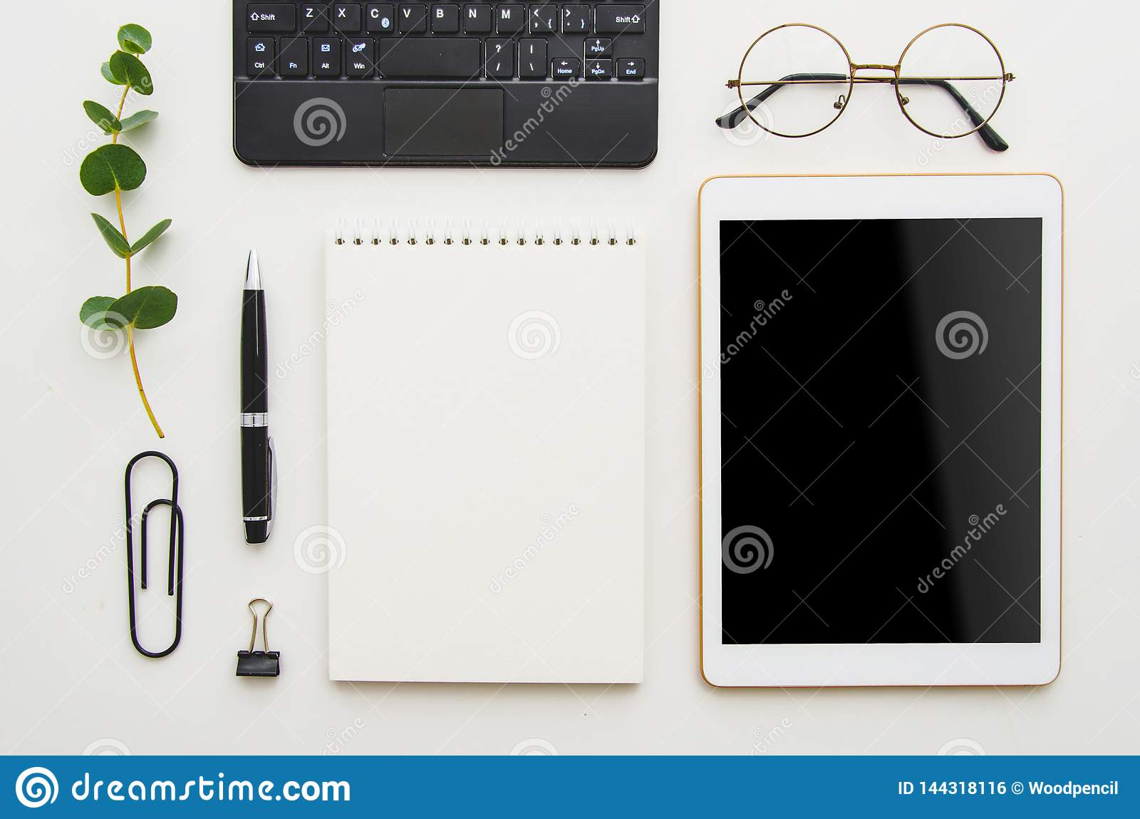 Flat lay work place. White office desk table with laptop, clips, glasses, notebook and pen. Top view with copy space