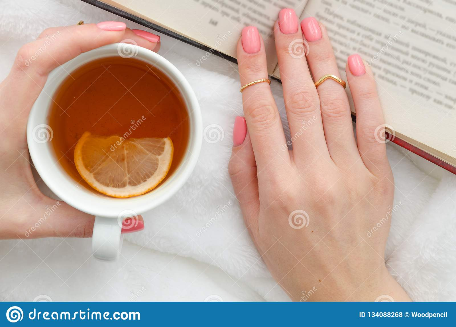 Flat Lay Young Woman Reading A Book And Holding Cup Of Tea With