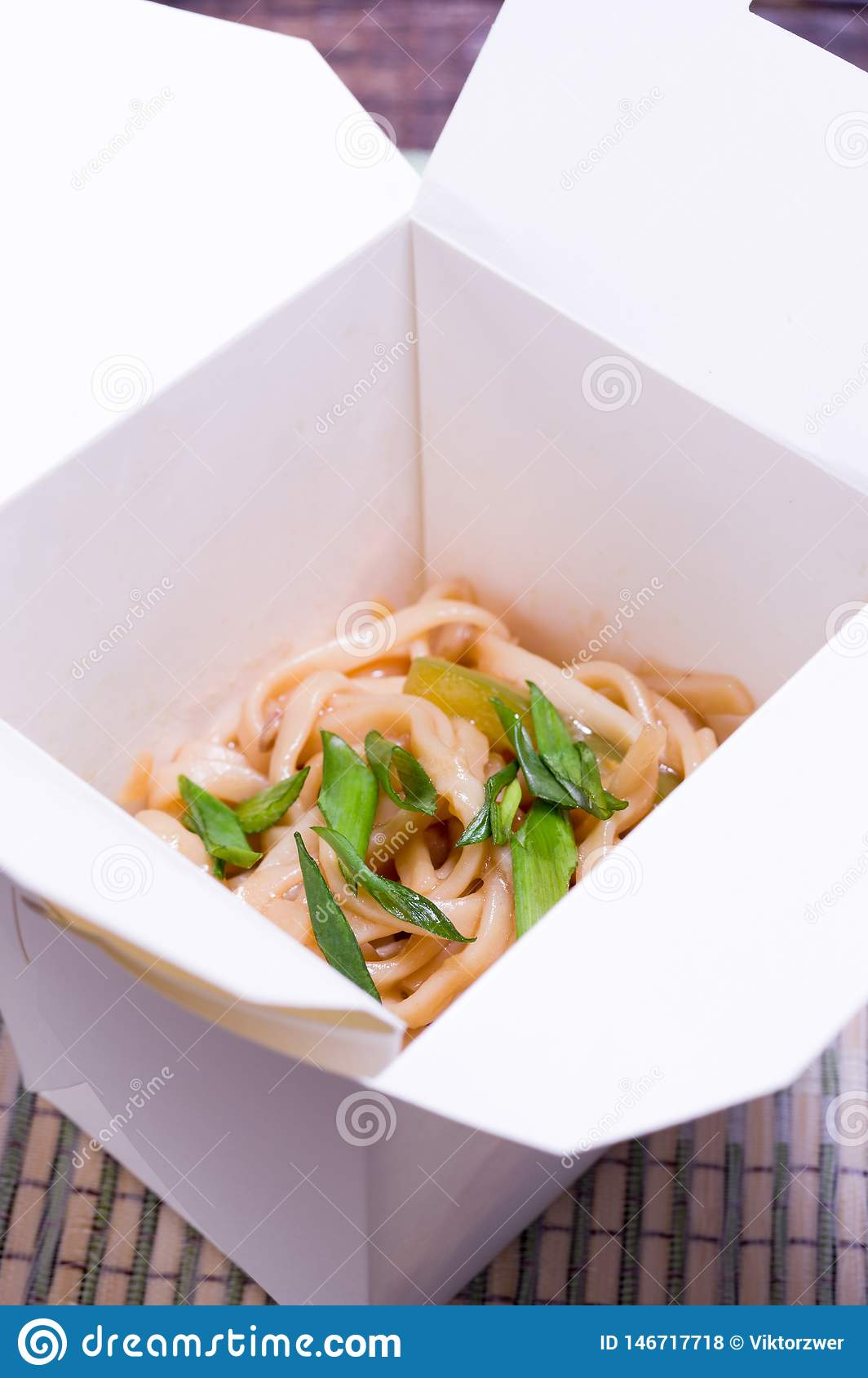 Flat noodles in a cardboard container. Vertical frame