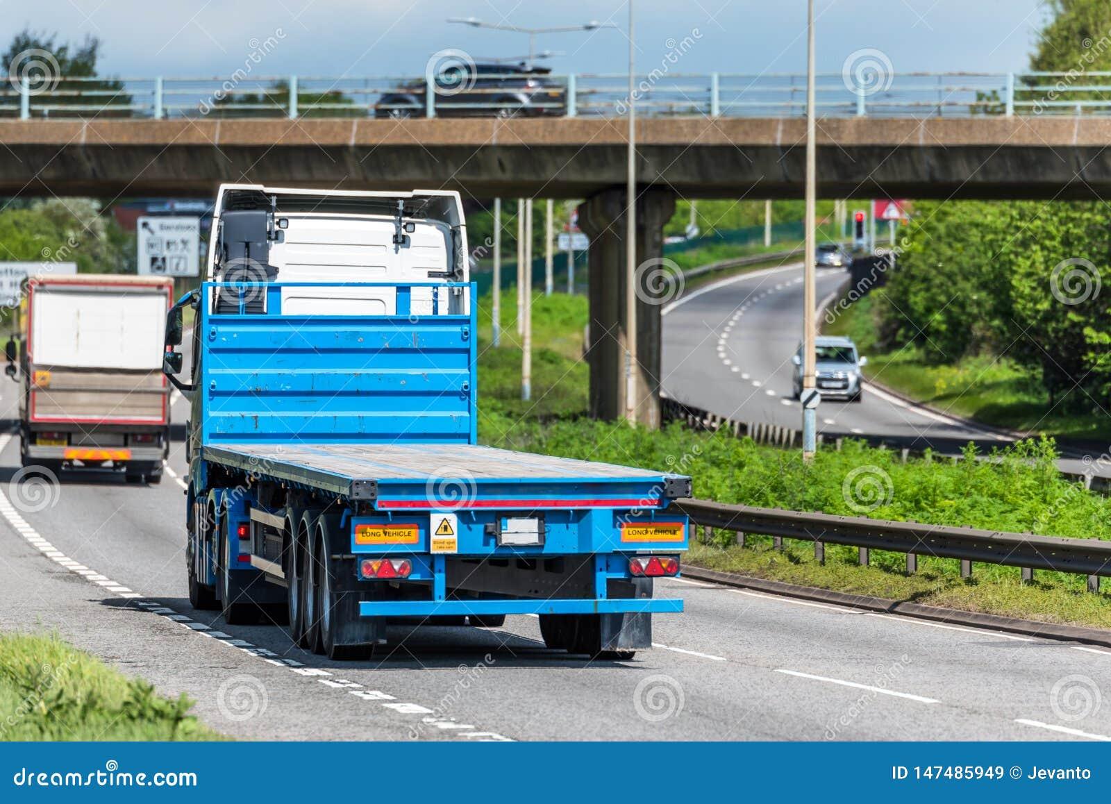 Flatbed vrachtwagenvrachtwagen op Britse autosnelweg in snelle motie