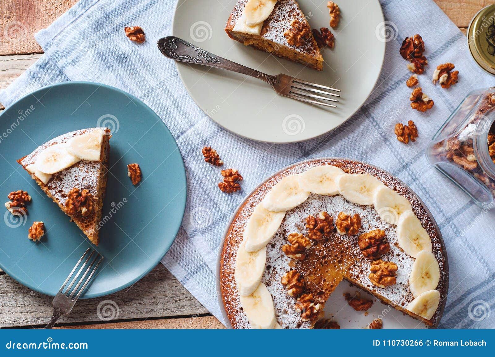 Flatlay avec le gâteau découpé en tranches de banane avec du sucre et la noix en poudre du plat avec le pot de fourchette et en v