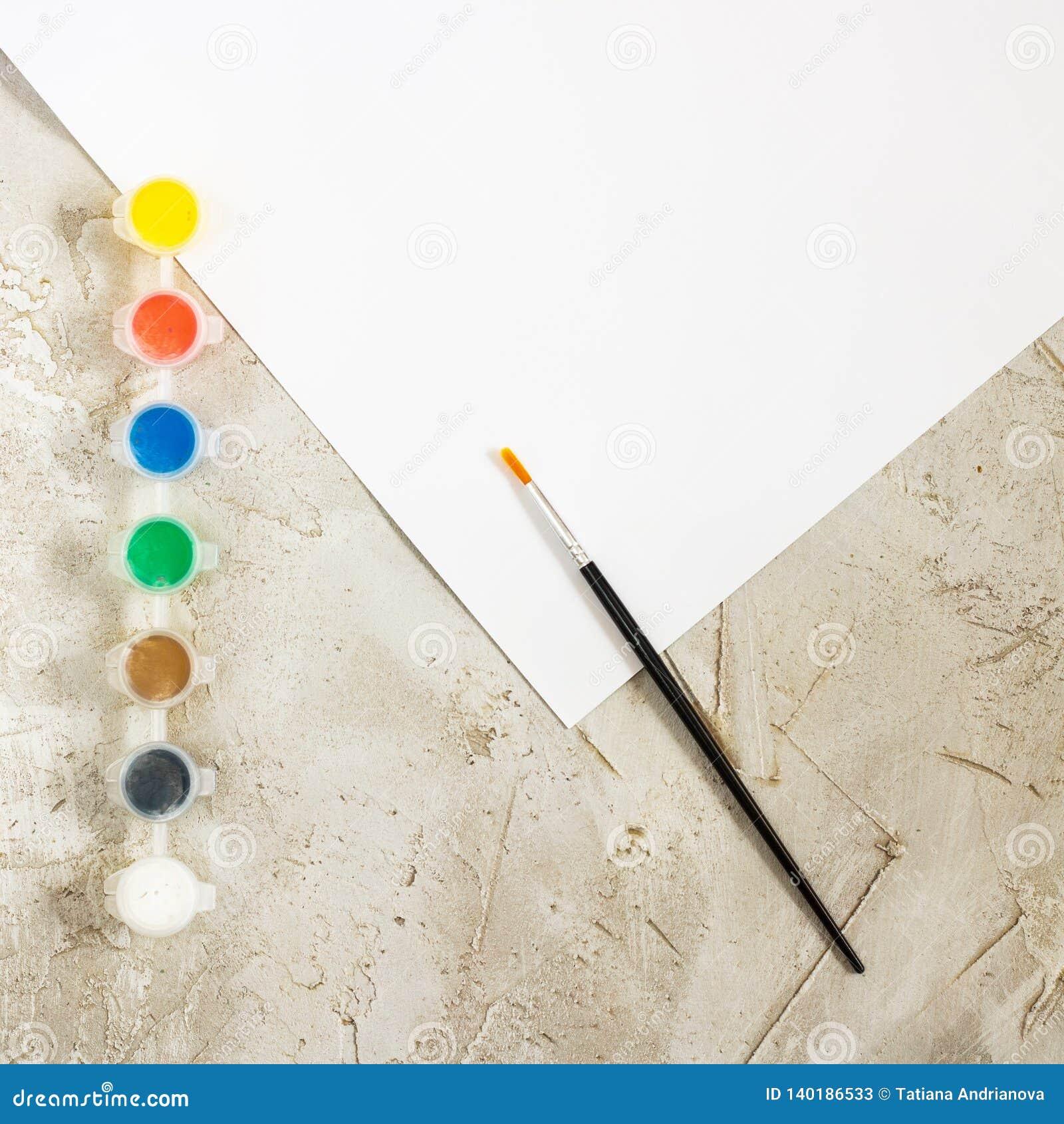 Flatlay com pinturas brilhantes, escova, e a folha de papel branca no fundo cinzento do cimento, espaço de trabalho, artista, des