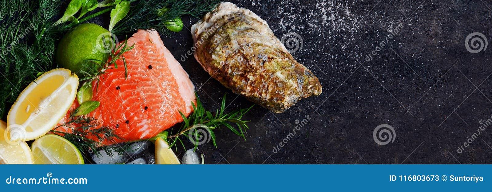 Flatlay Composizione di frutti di mare freschi su un fondo scuro Trota ed ostriche con le erbe ed il limone