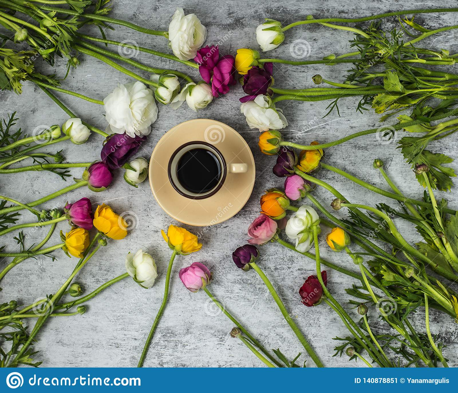 Flatlay de flores da mola e de copo do café preto no fundo de mármore cinzento