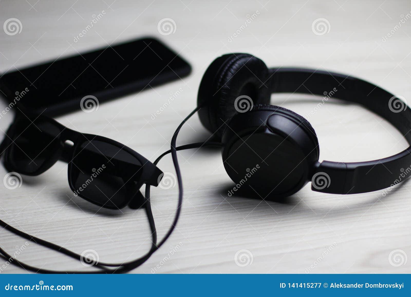 Flatlay des schwarzen Telefons, der Kopfhörer und des Glases