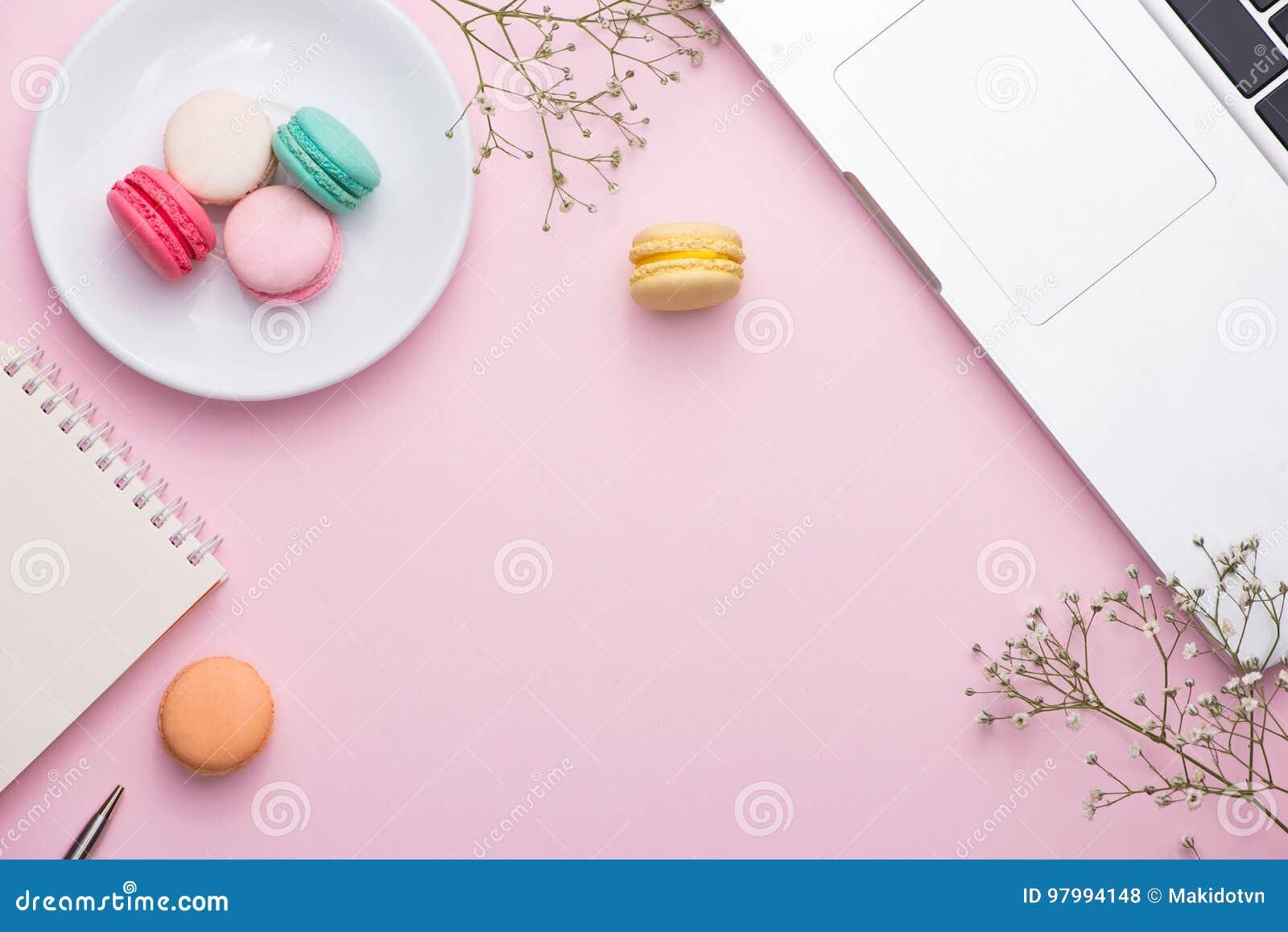Flatlay do portátil, macaron do bolo e copo do chá na tabela cor-de-rosa Seja