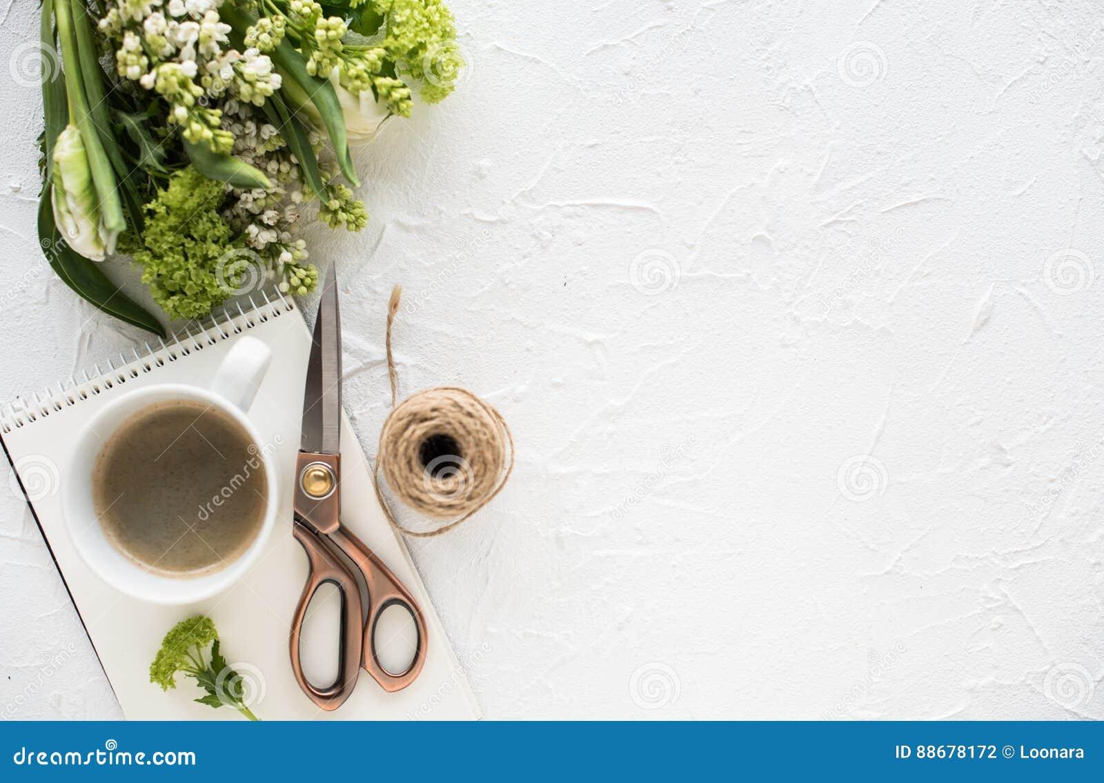 Flatlay féminin avec des fleurs et ccoffee sur le dessus de table blanc