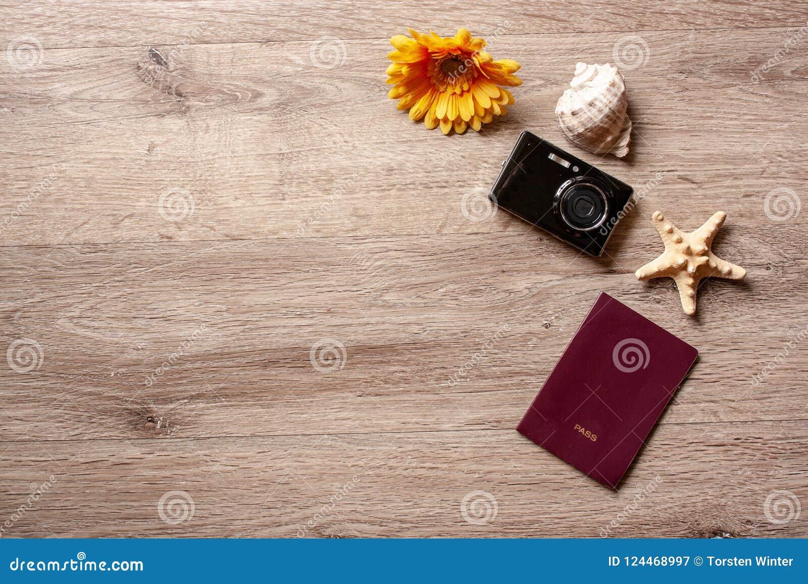 Flatlay ferie/travel tema med brun bakgrund med kameran, passet, skalet, sjöstjärnan och blommor