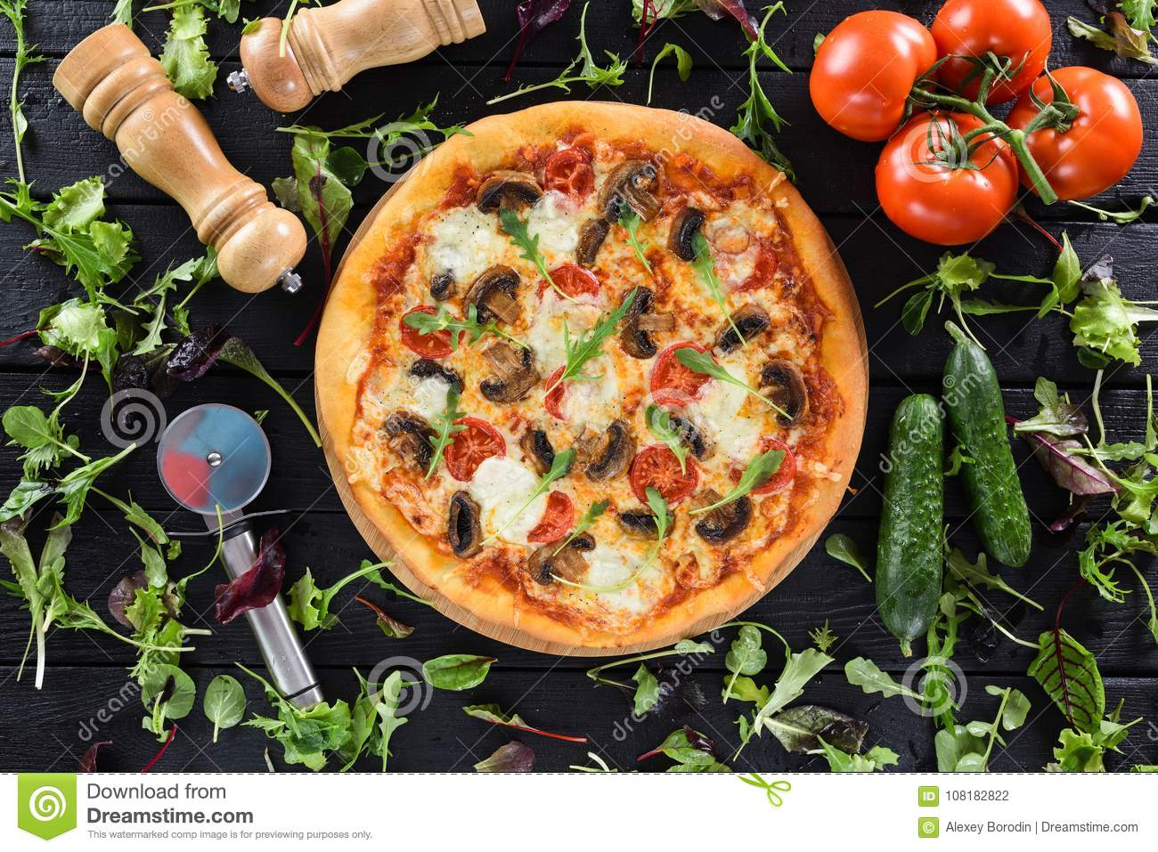 Flatlay of healthy vegetable mushroom pizza served with fresh vegetables, greens, pizza cutter and salt shaker on black background