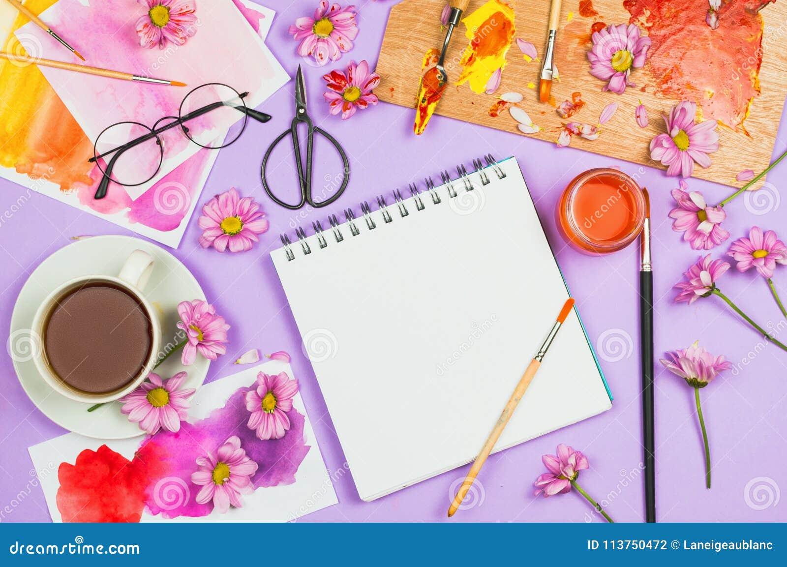 Flatlay met kunstlevering, kunstenaarspalet, glazen, bloemen, kop thee en sketchbook met blanco pagina