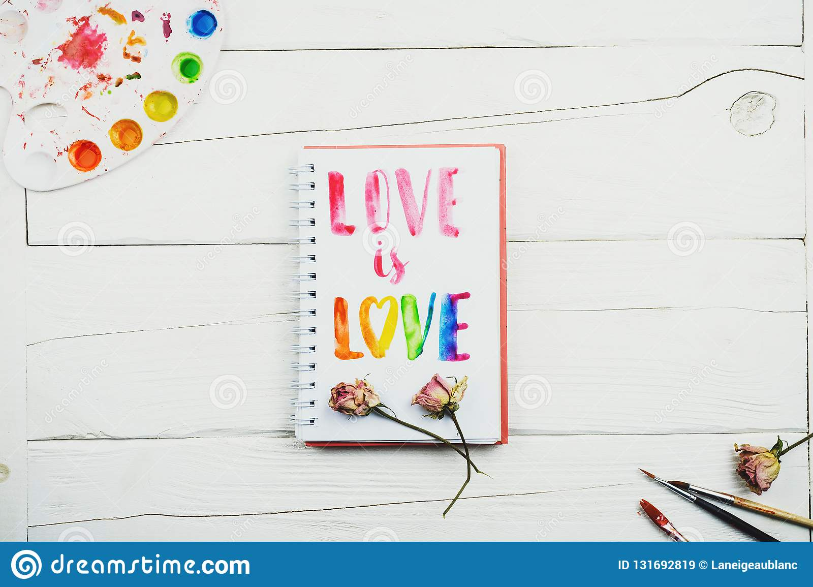 Flatlay of sketchbook with handlettering inscription `Love is love`