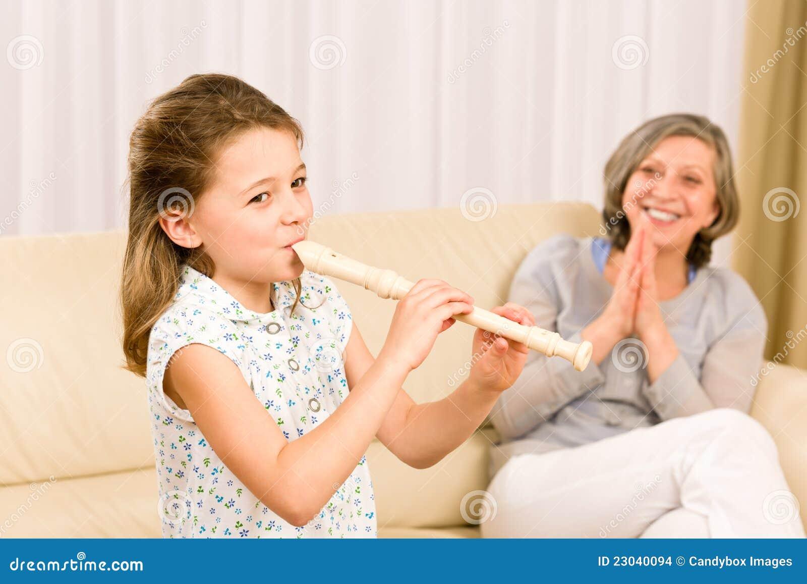 Flauta del juego de la chica joven con la abuela orgullosa