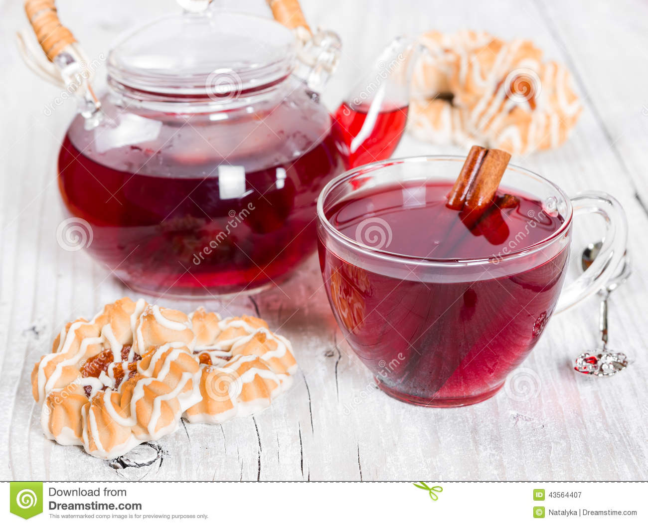 Flavored fruit tea with cookies on wooden background.