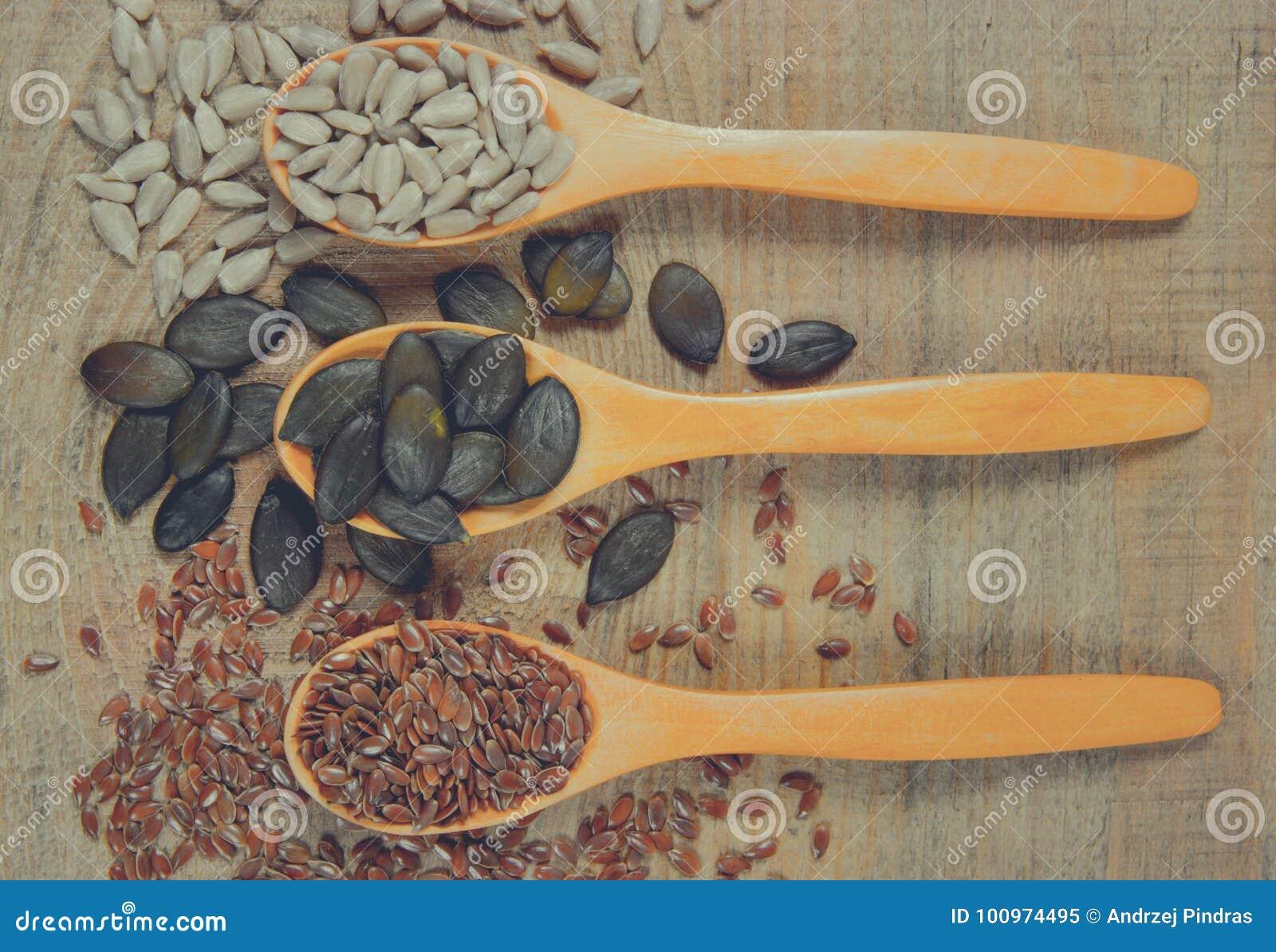 Flaxseed, bania i słonecznikowi ziarna w drewnianych łyżkach,