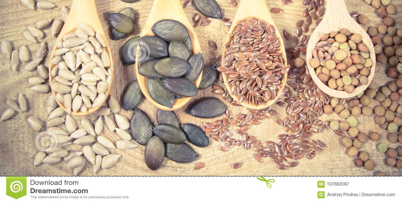 Flaxseed, bania, rodzynki, soczewicy i słonecznikowi ziarna w drewnianych łyżkach,
