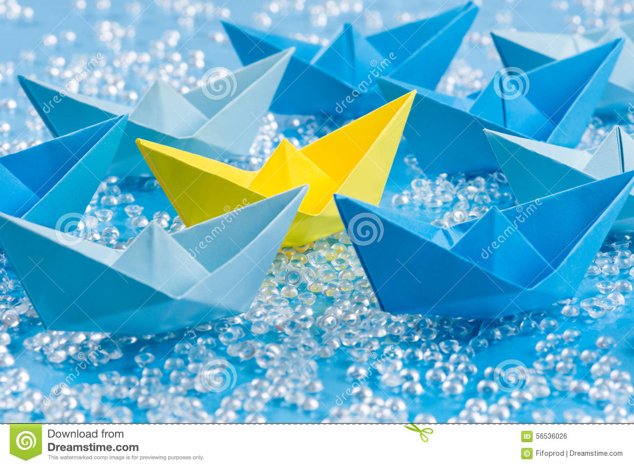 Fleet of blue Origami paper ships on blue water like background surrounding a yellow one