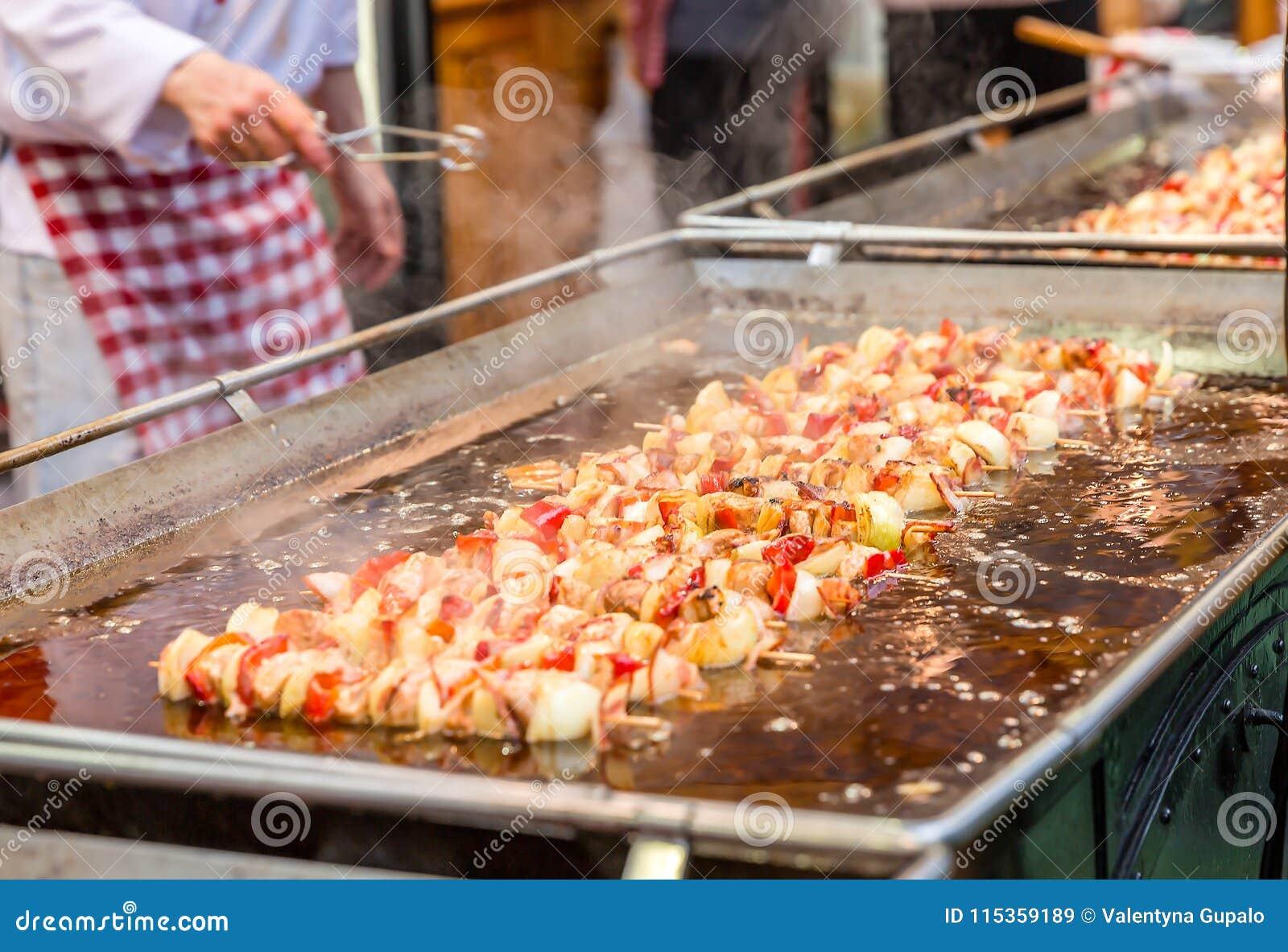 Fleisch und Gemüse auf den hölzernen Stöcken, die in kochendem Öl an der Messe braten Straßenlebensmittel