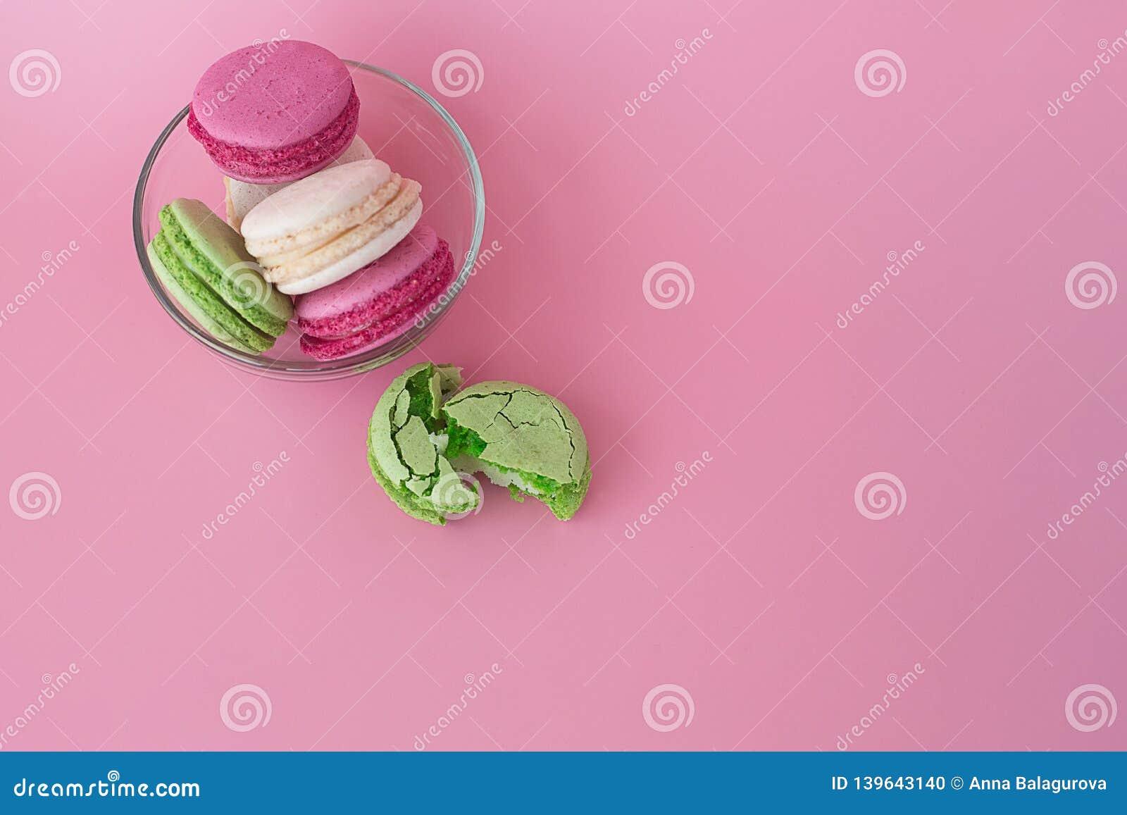 Flera mång--färgade macarons i en exponeringsglasplatta på en rosa bakgrund