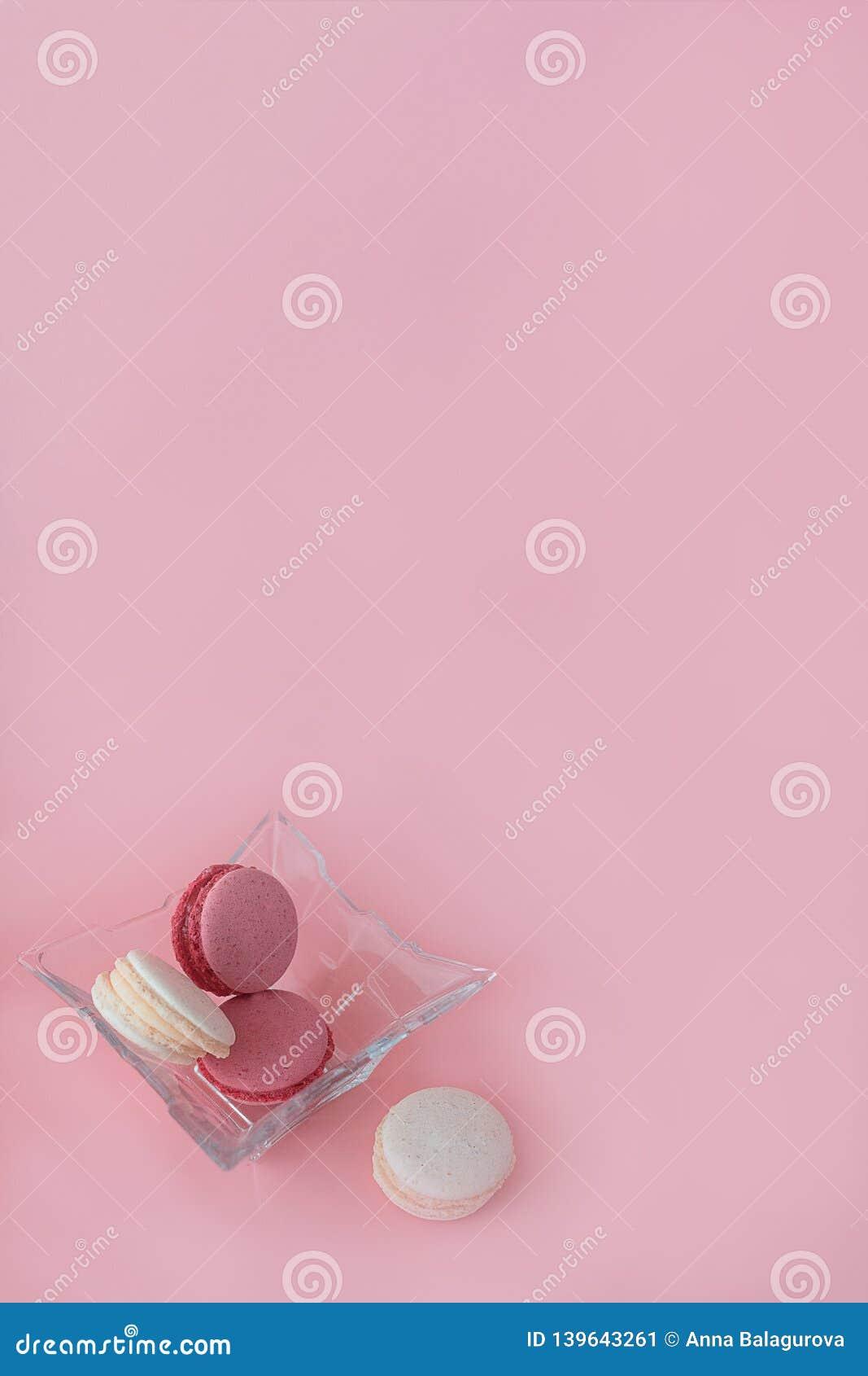 Flera mång--färgade macarons i en exponeringsglasplatta på en rosa orange bakgrund