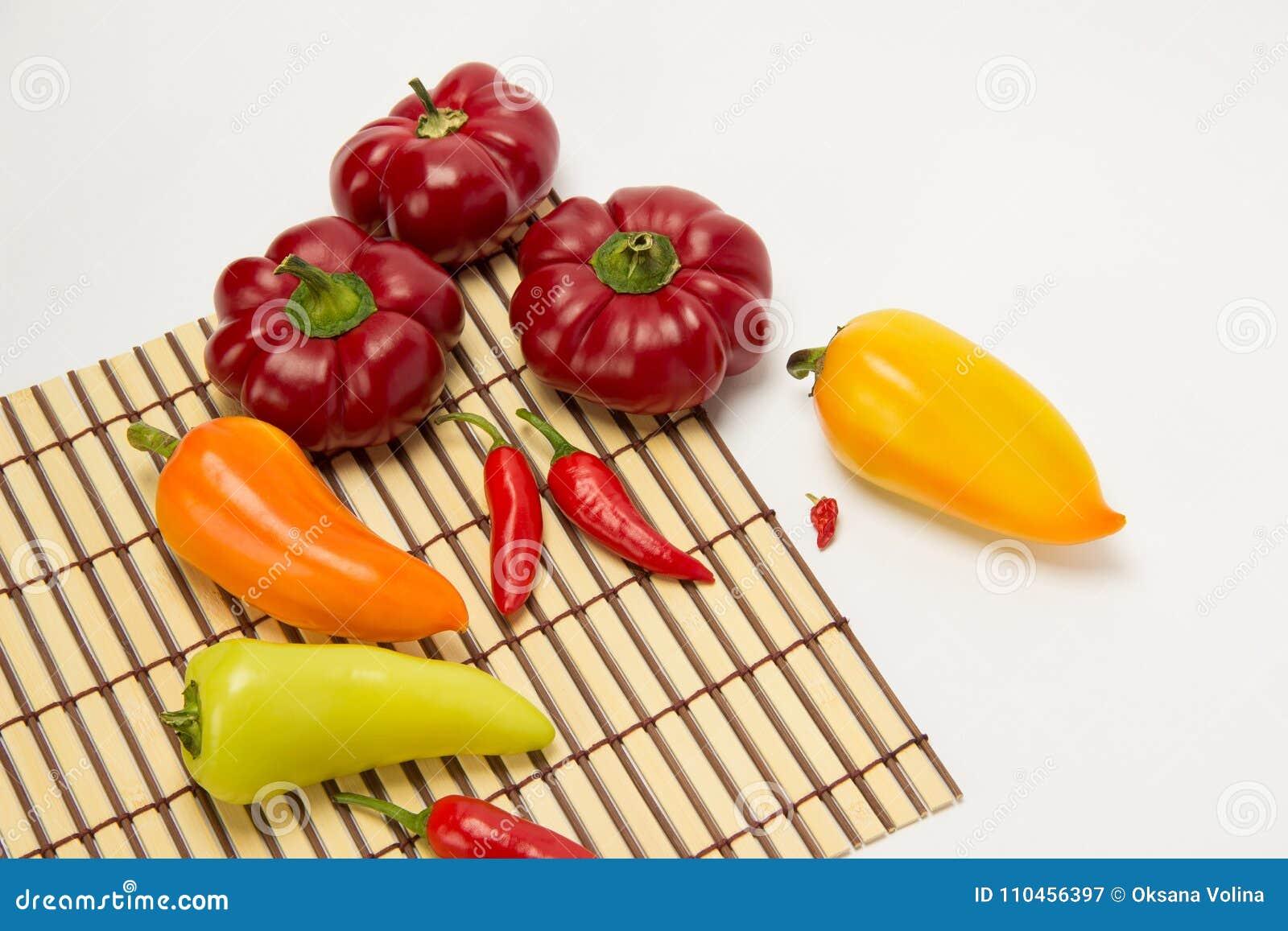 Flera mogen sötsak och varma peppar på en sugrörservett på en vit
