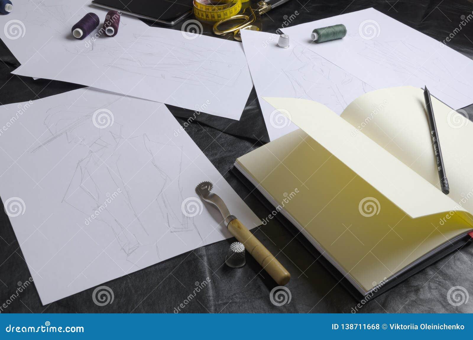Flera skissar under formgivarens arbete på tabellen Hjälpmedel för att skapa klädersamlingen