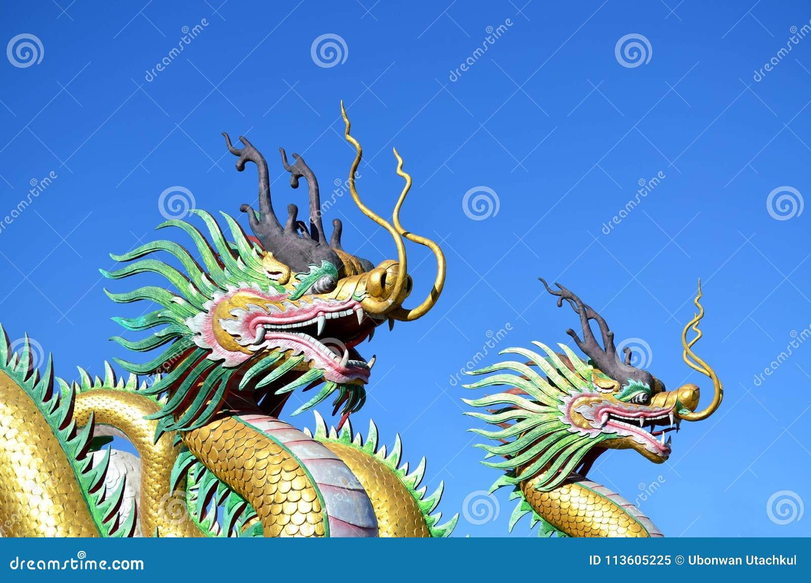 Flerfärgat av två kinesiska drakestatyer mot blå himmel