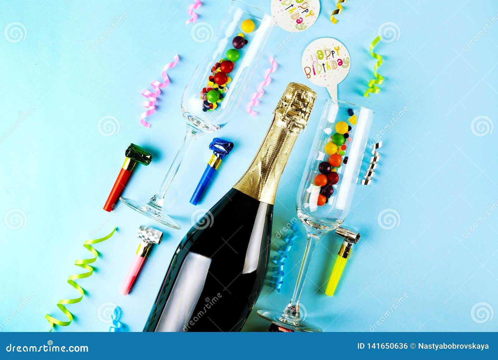 Fles champagne, paar fluitglazen, wimpels, kaarsen & andere partijeigenschappen op heldere roze document achtergrond toespraak