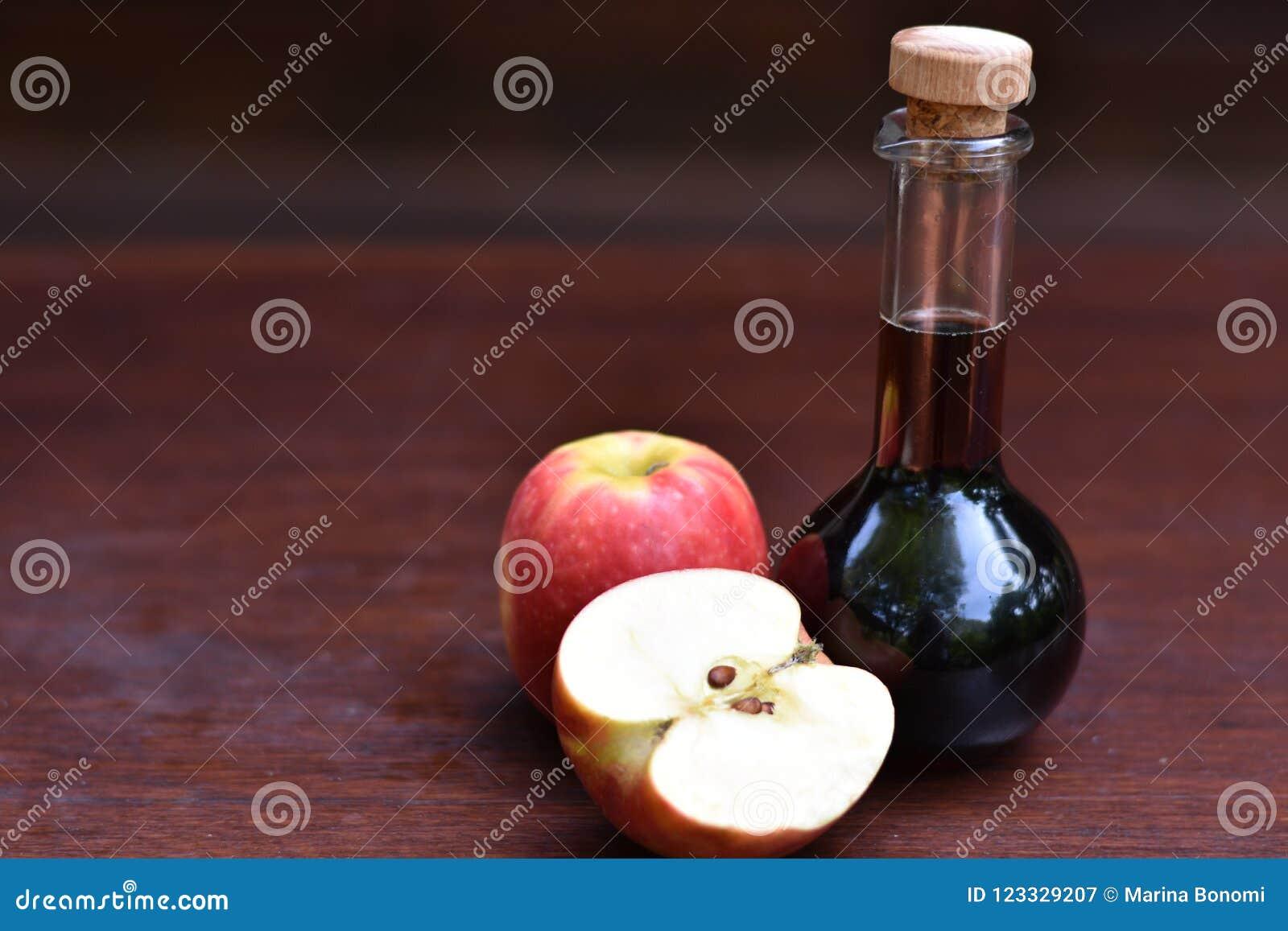 Fles de azijn van de appelcider naast rijpe appelen