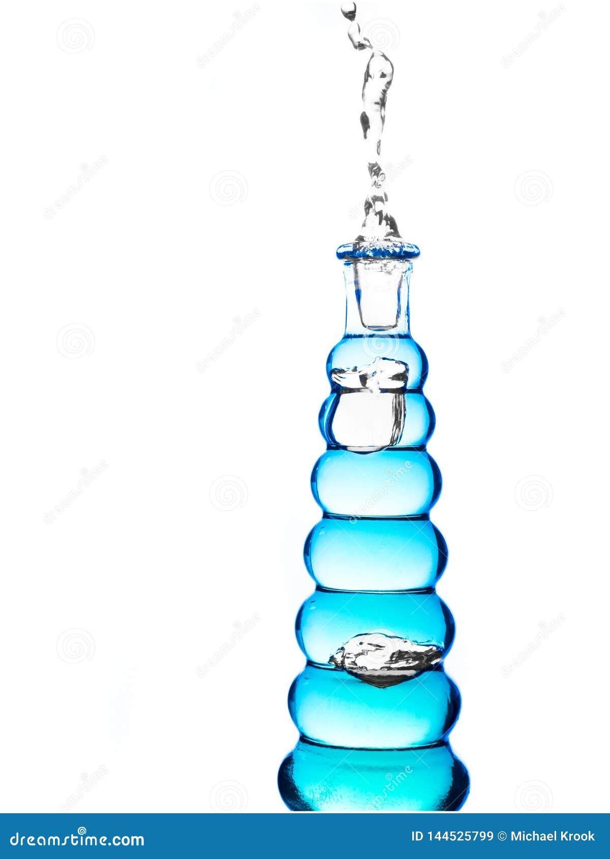 Fles met blauw water die uitgieten