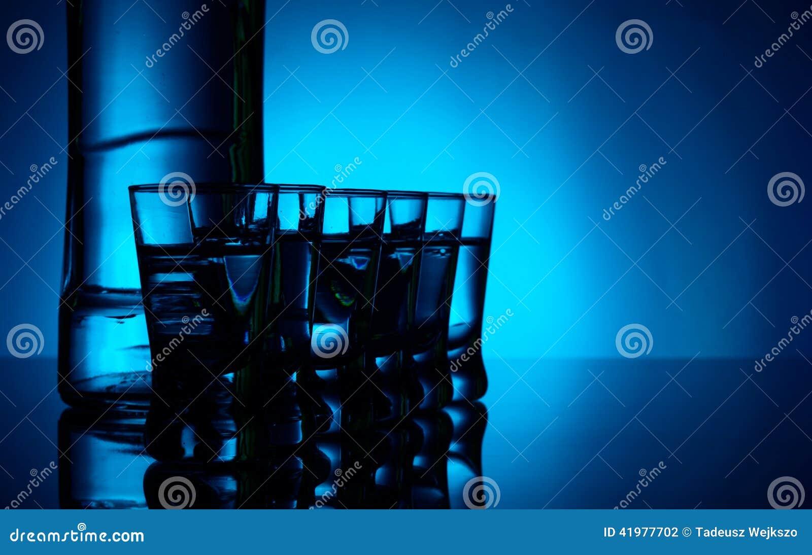 Fles wodka met vele die glazen met blauwe backlight worden aangestoken