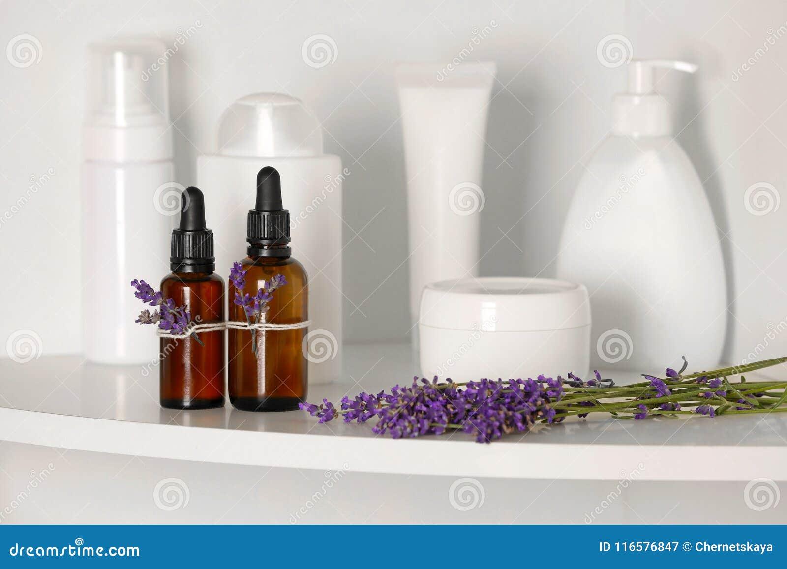 Flessen etherische olie met lavendel op plank
