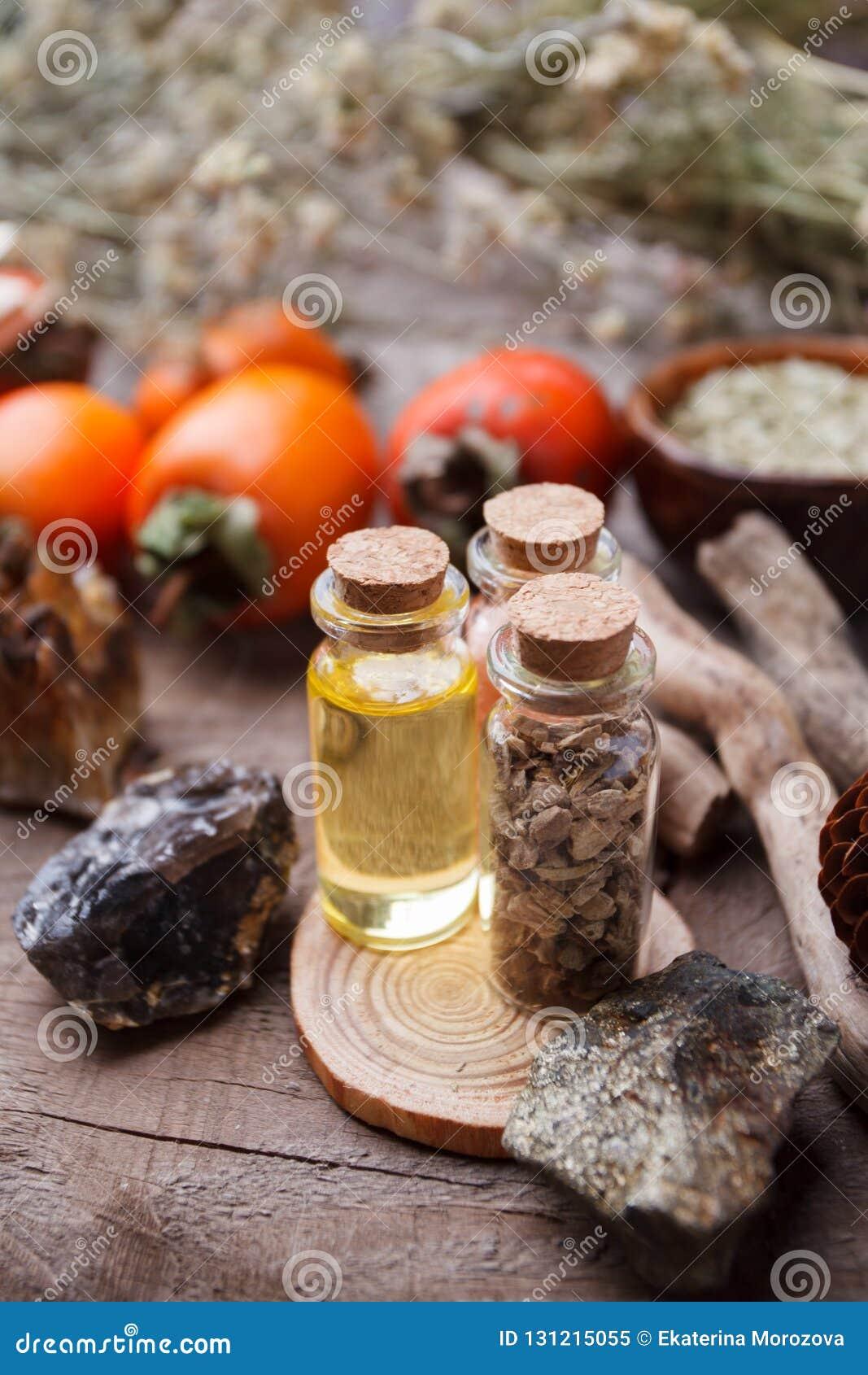 Flessen met kruiden, droge bloemen, stenen en magische voorwerpen op heksen houten lijst