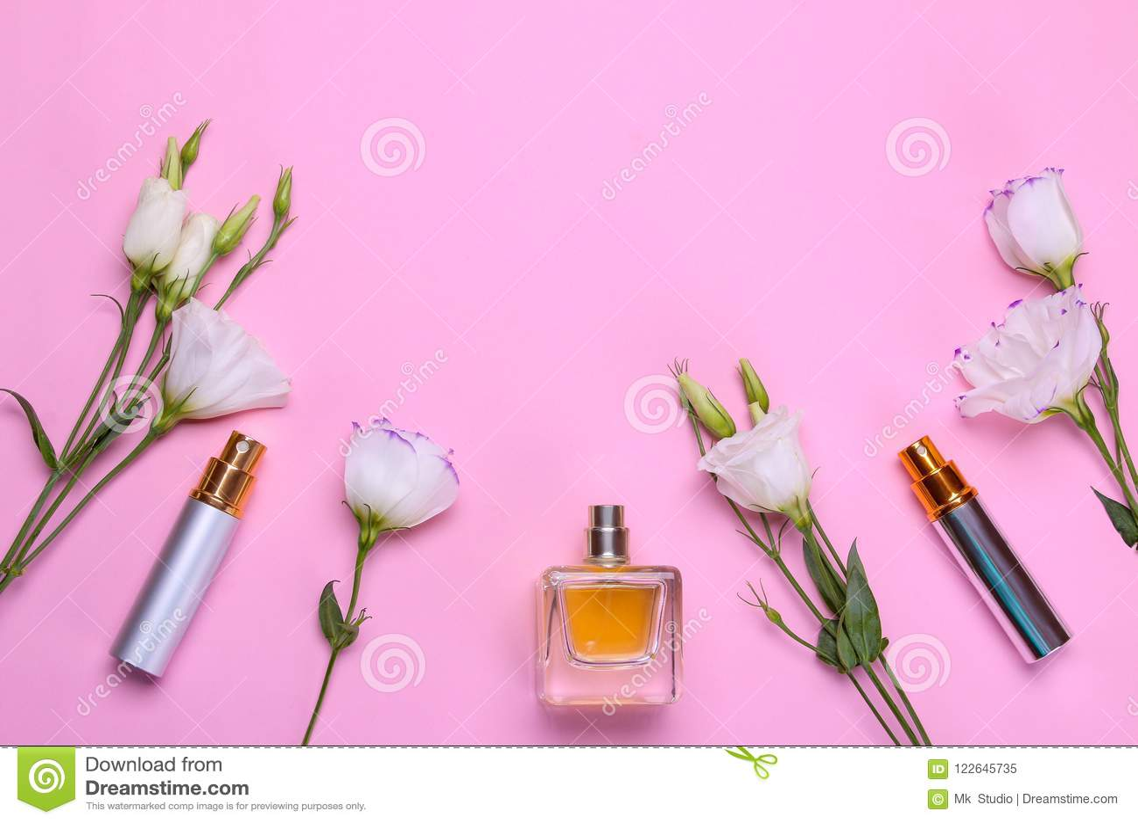 Flessen van parfum en mooie bloemeneustoma op een heldere roze achtergrond Vrouwen` s toebehoren Hoogste mening