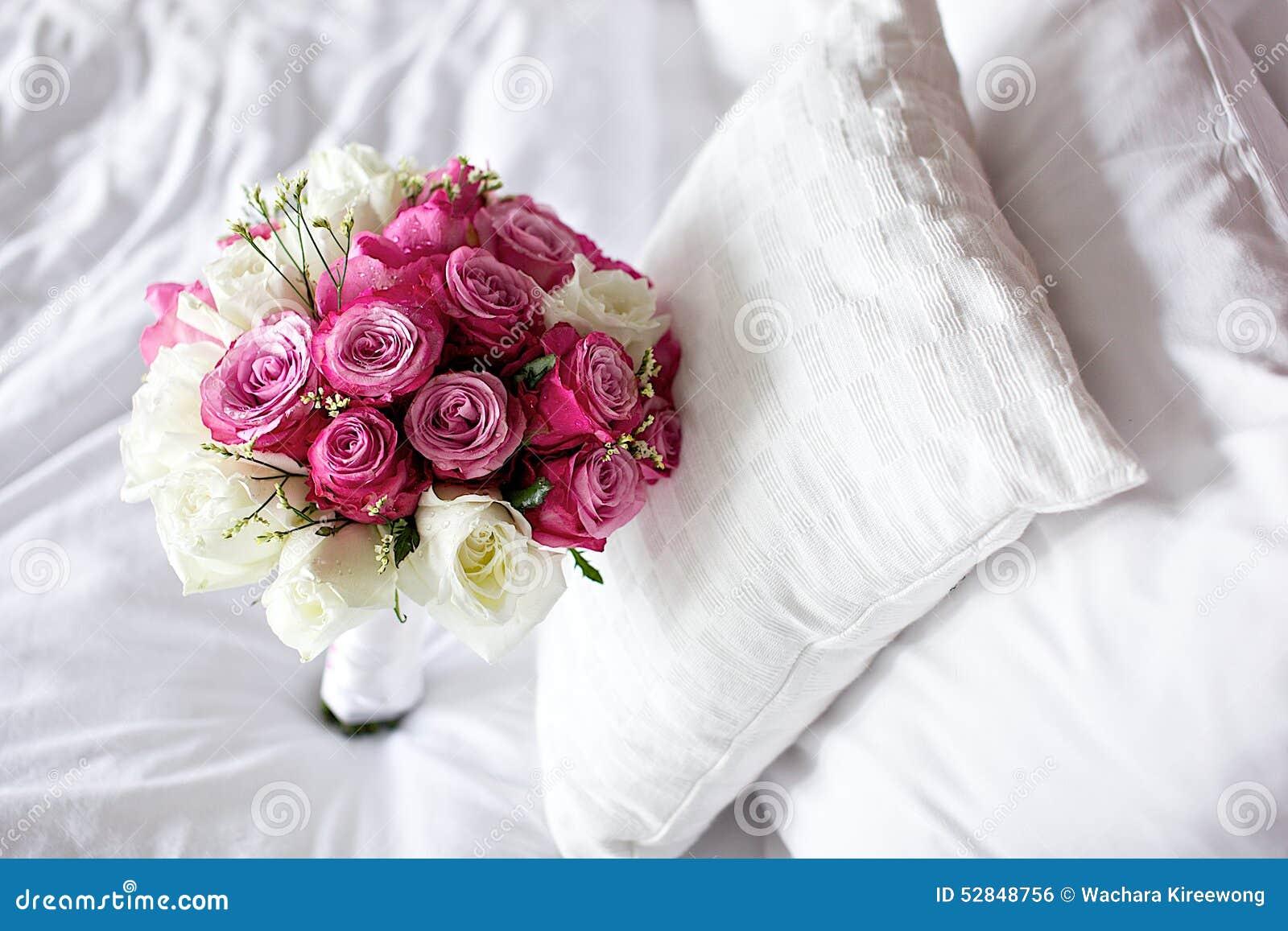 bouquet de mariage de fleur de rose de blanc sur le lit photo