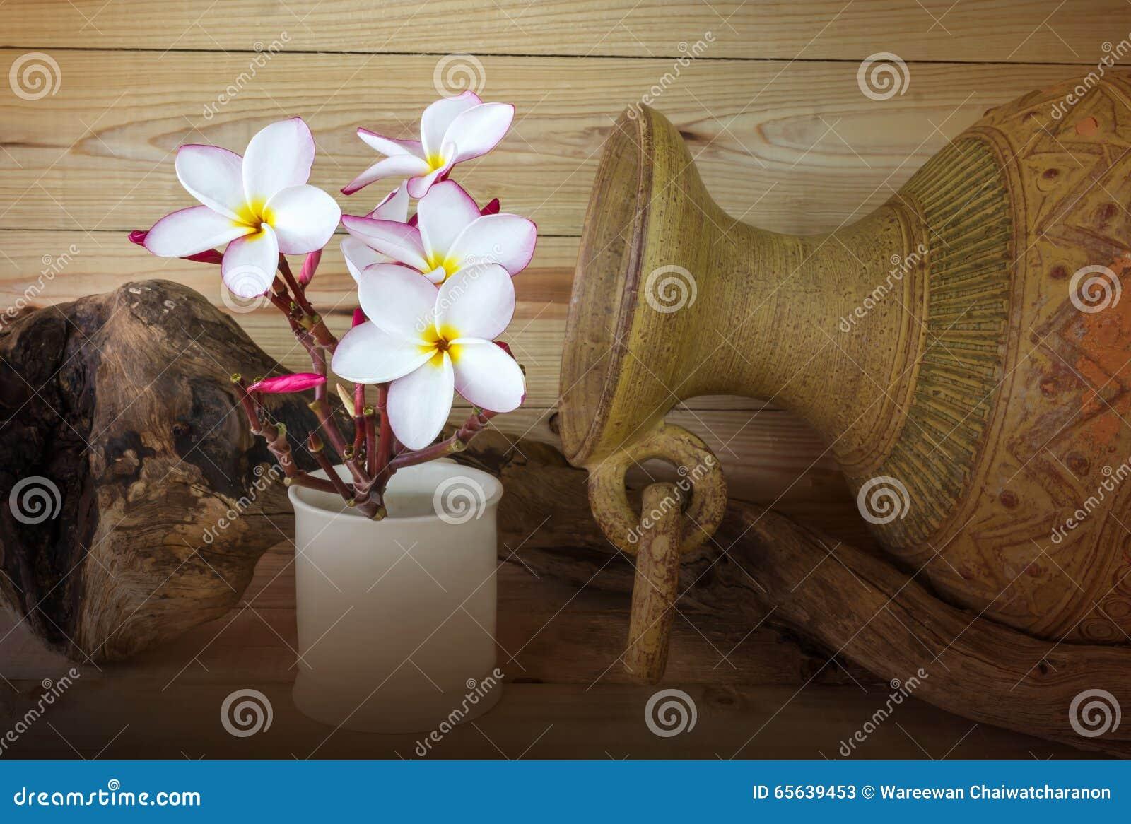 Fleur rose de Frangipani et vase cuit au four à argile dans le St de vintage et de station thermale