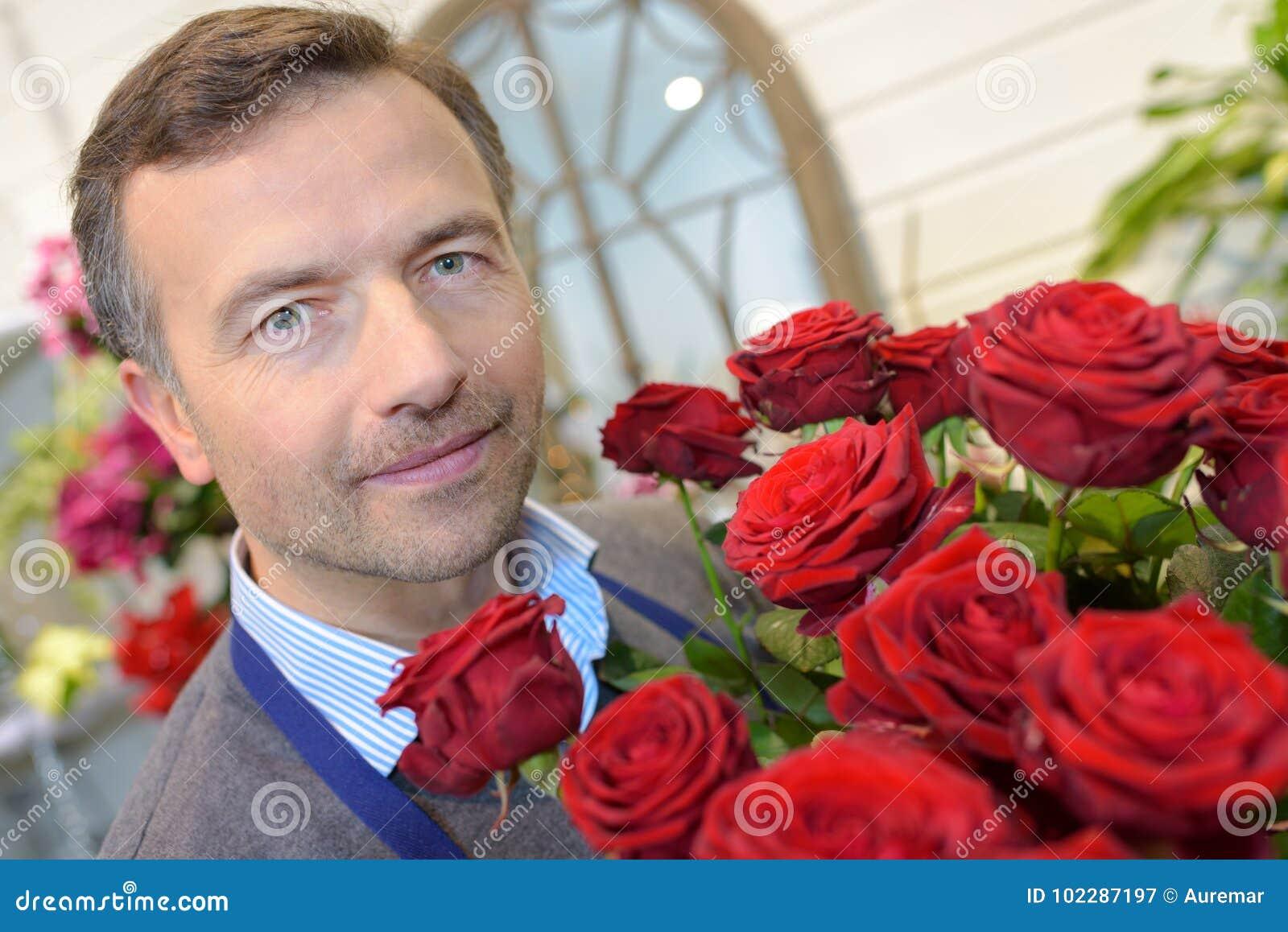 Fleuriste masculin tenant de belles roses de bouquet