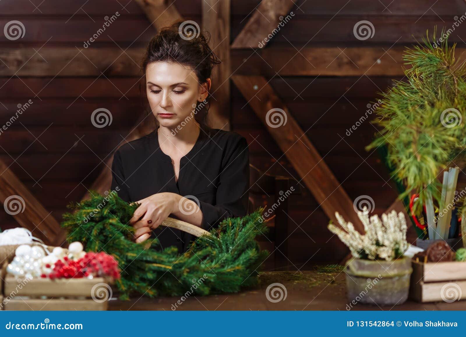 Fleuriste travaillant Woman avec la guirlande de Noël Jeune concepteur de sourire mignon de femme préparant la guirlande à feuill
