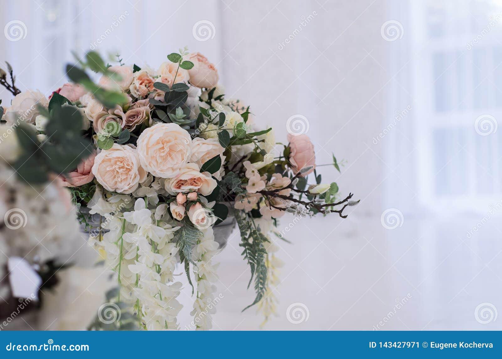 Fleurs artificielles élégantes dans un support en verre de vase sur un plancher
