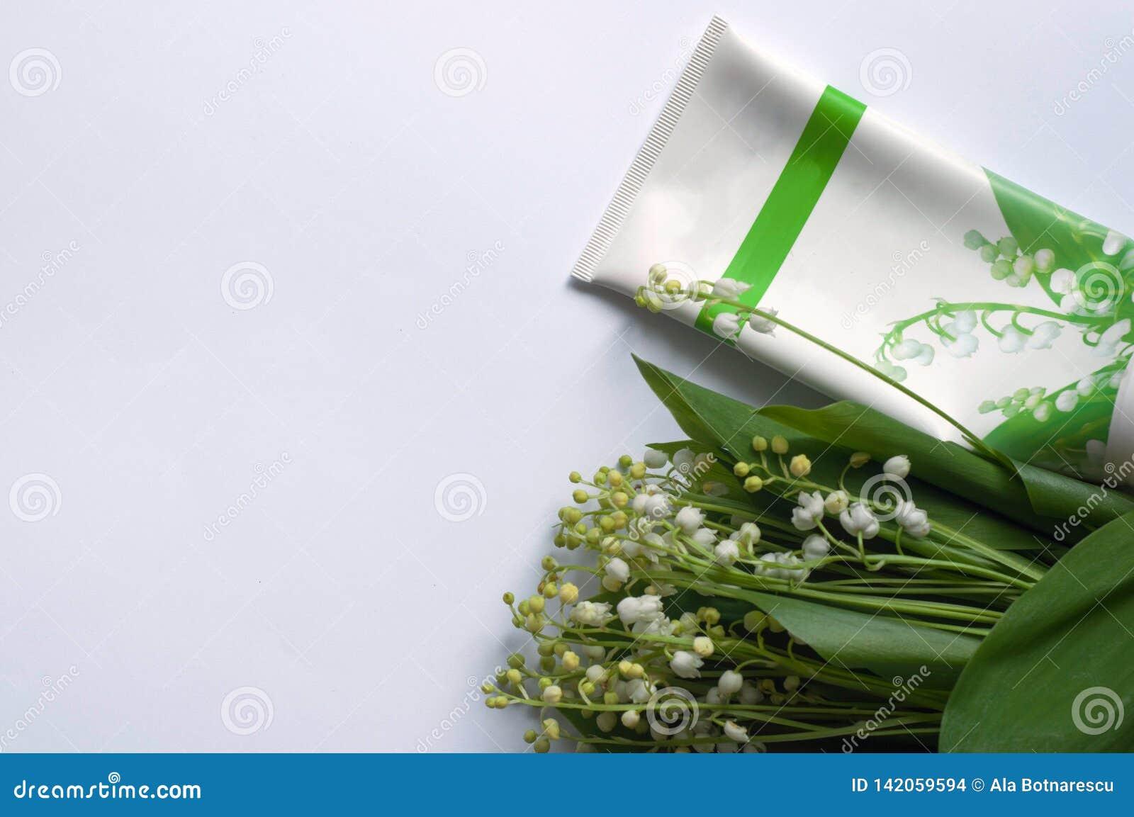 Fleurs cosmétiques de crème et du muguet sur le fond blanc